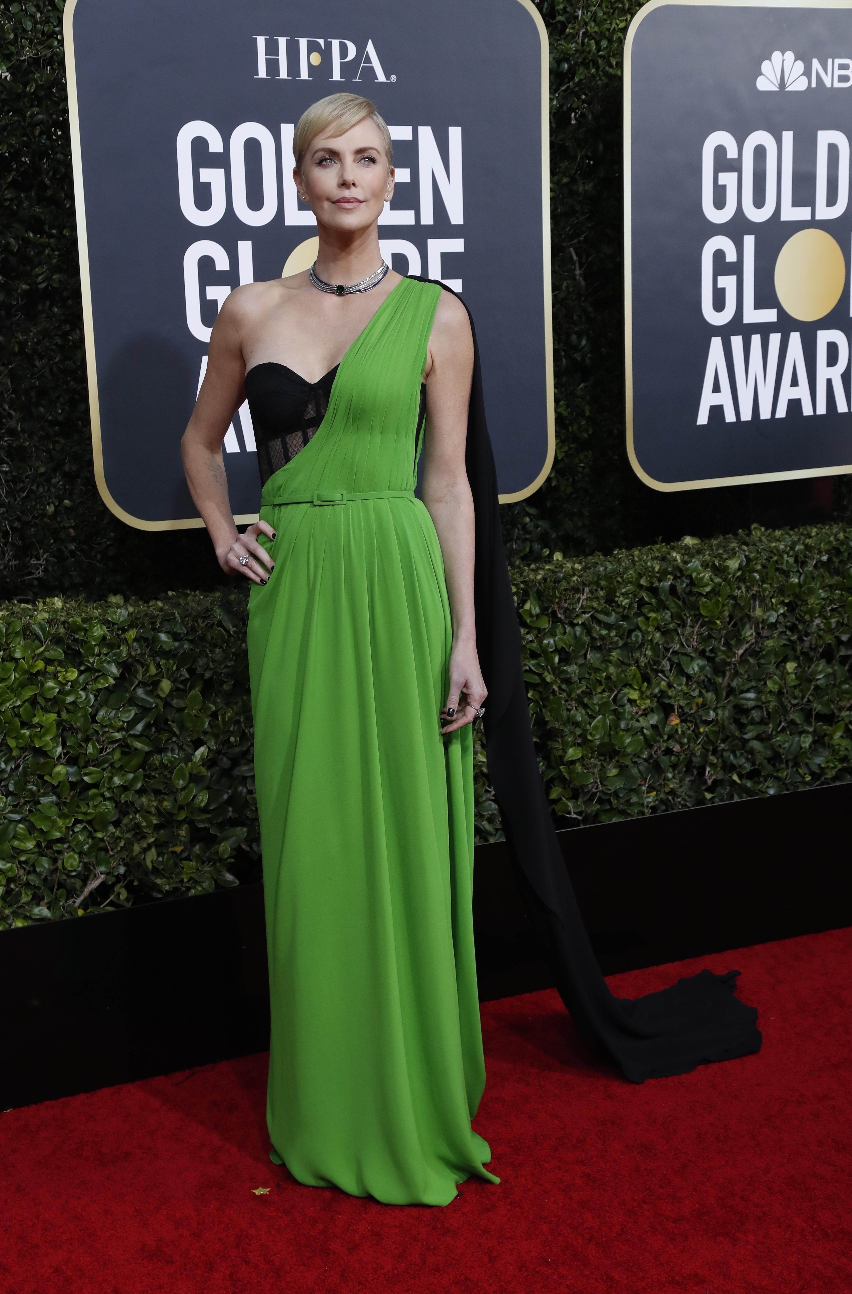 Charlize Theron lució un vestido bicolor en verde y negro con bustier by Christian Dior y capa a tono. Completó su look con una gargantilla con esmeralda y brillantes