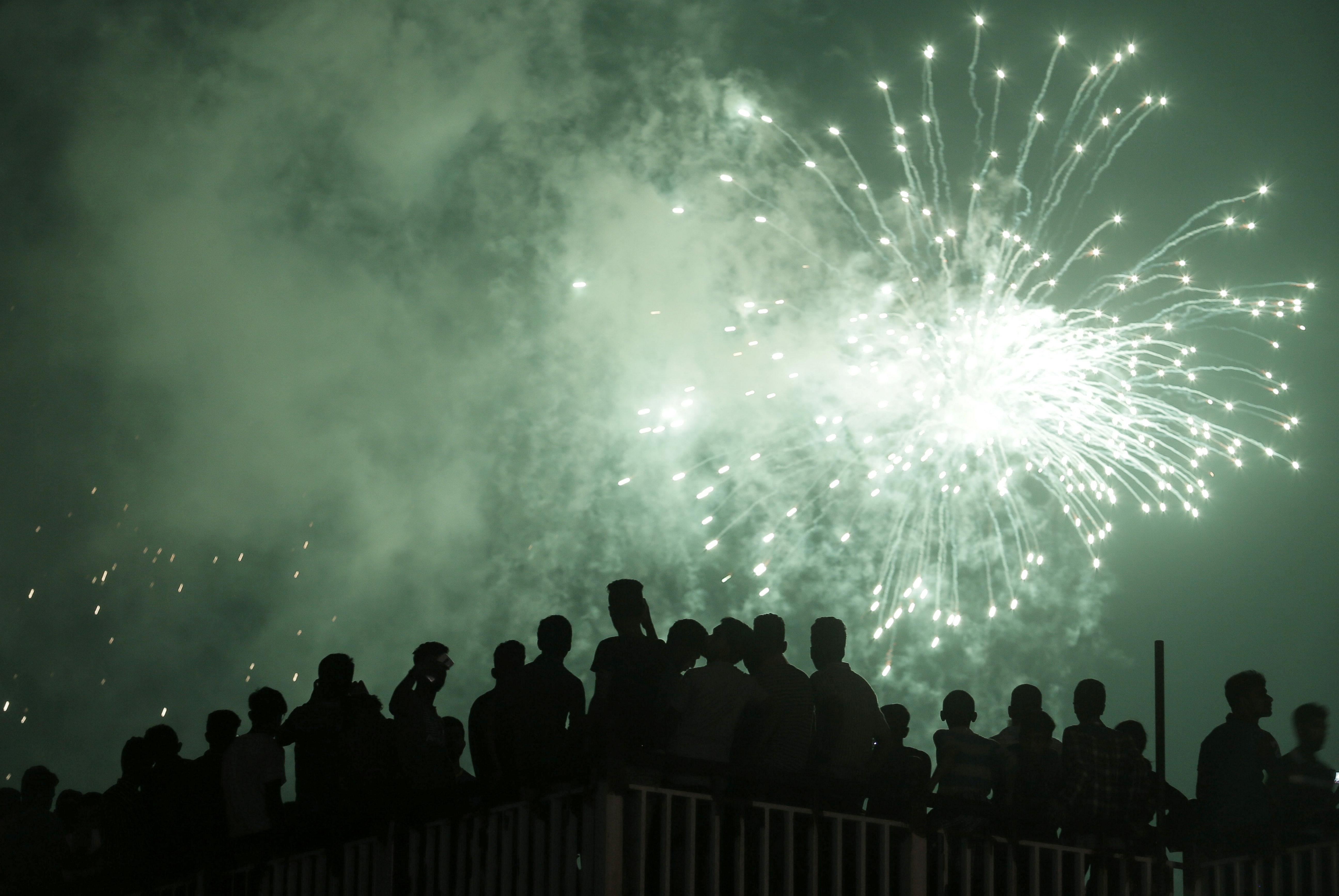 La gente ve los fuegos artificiales durante las celebraciones de Año Nuevo en Colombo, Sri Lanka (REUTERS/Dinuka Liyanawatte)