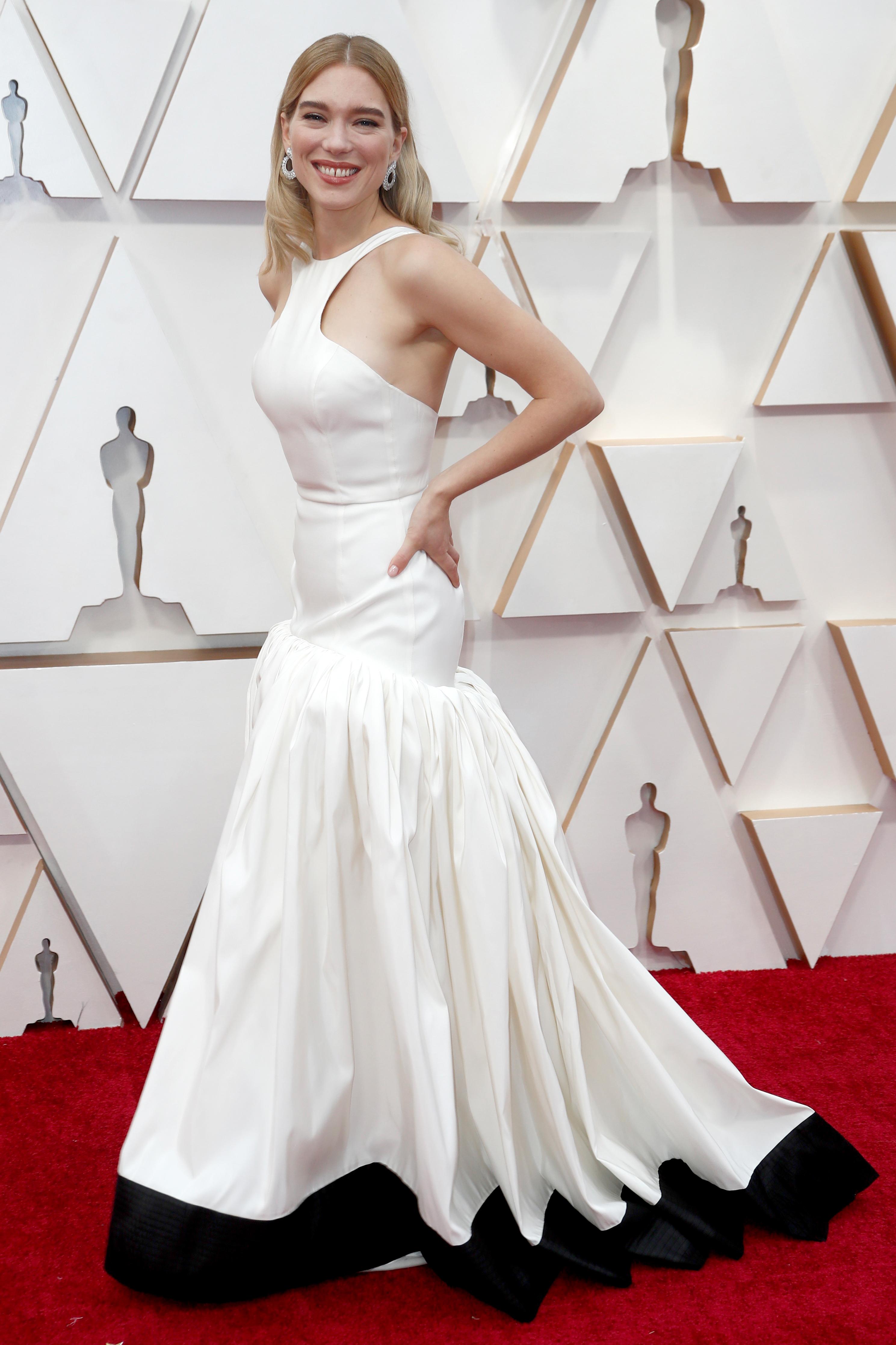 Lea Seydoux lució un diseño de cuello halter en blanco con detalles en su falda en la parte inferior de color negro. Completó el look con aros XXL en dorado