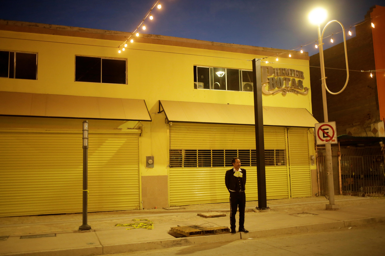 Un músico se encuentra en la calle que conduce al Puente Internacional Paso del Norte, donde el flujo de personas ha disminuido, ya que las nuevas restricciones de viaje destinadas a contener la enfermedad por coronavirus (COVID-19) han impedido que millones de mexicanos que viven cerca de la frontera con EE. UU. cruce de ida y vuelta, en Ciudad Juárez, México 29 de marzo de 2020.
