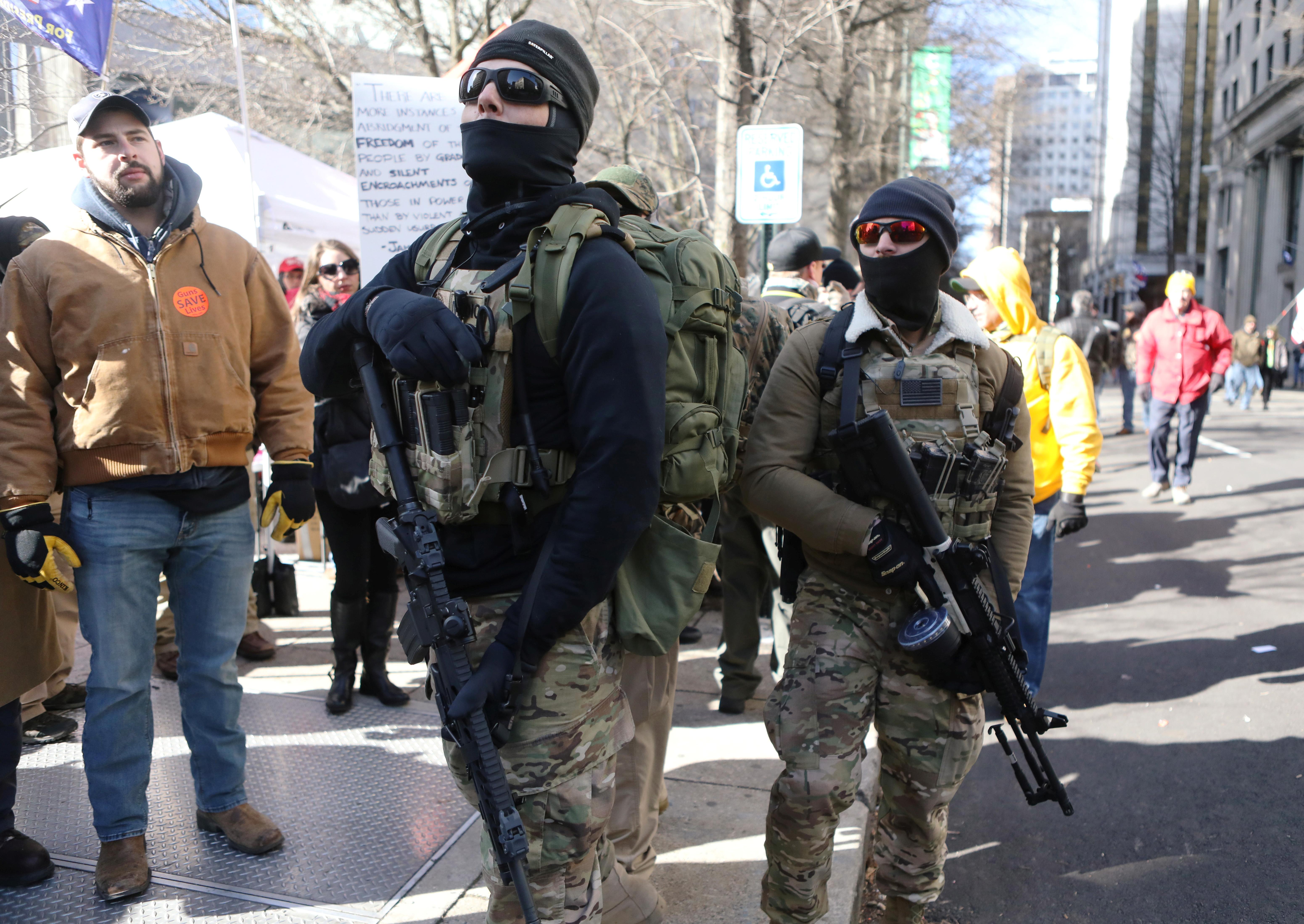 Estos dos hombres llevan los rostros cubiertos, y portan fusiles de la familia del AR-15 (REUTERS/Jim Urquhart)