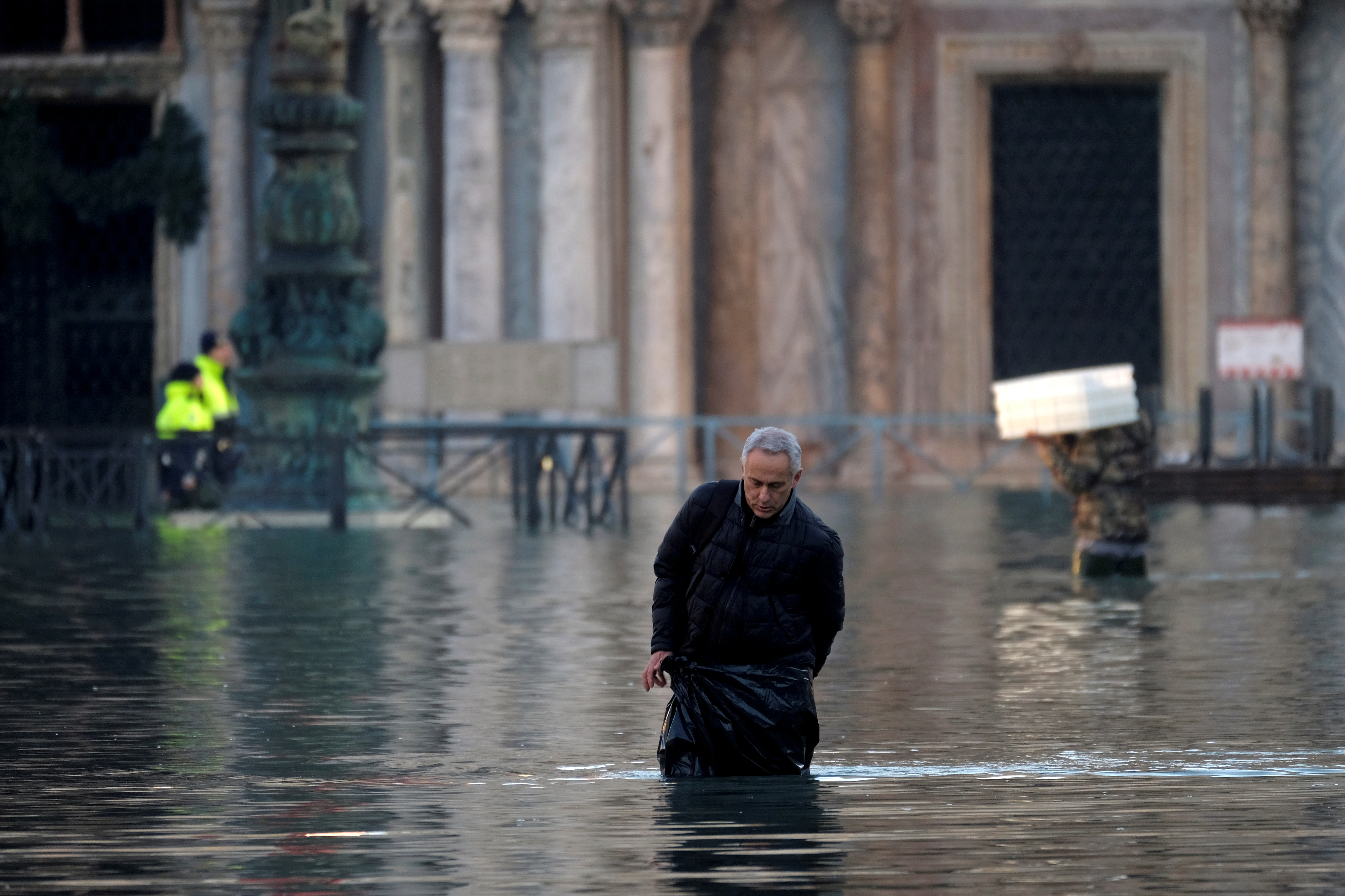 Un hombre camina a través de una calle inundada hacia la Plaza de San Marcos (REUTERS/Manuel Silvestri)