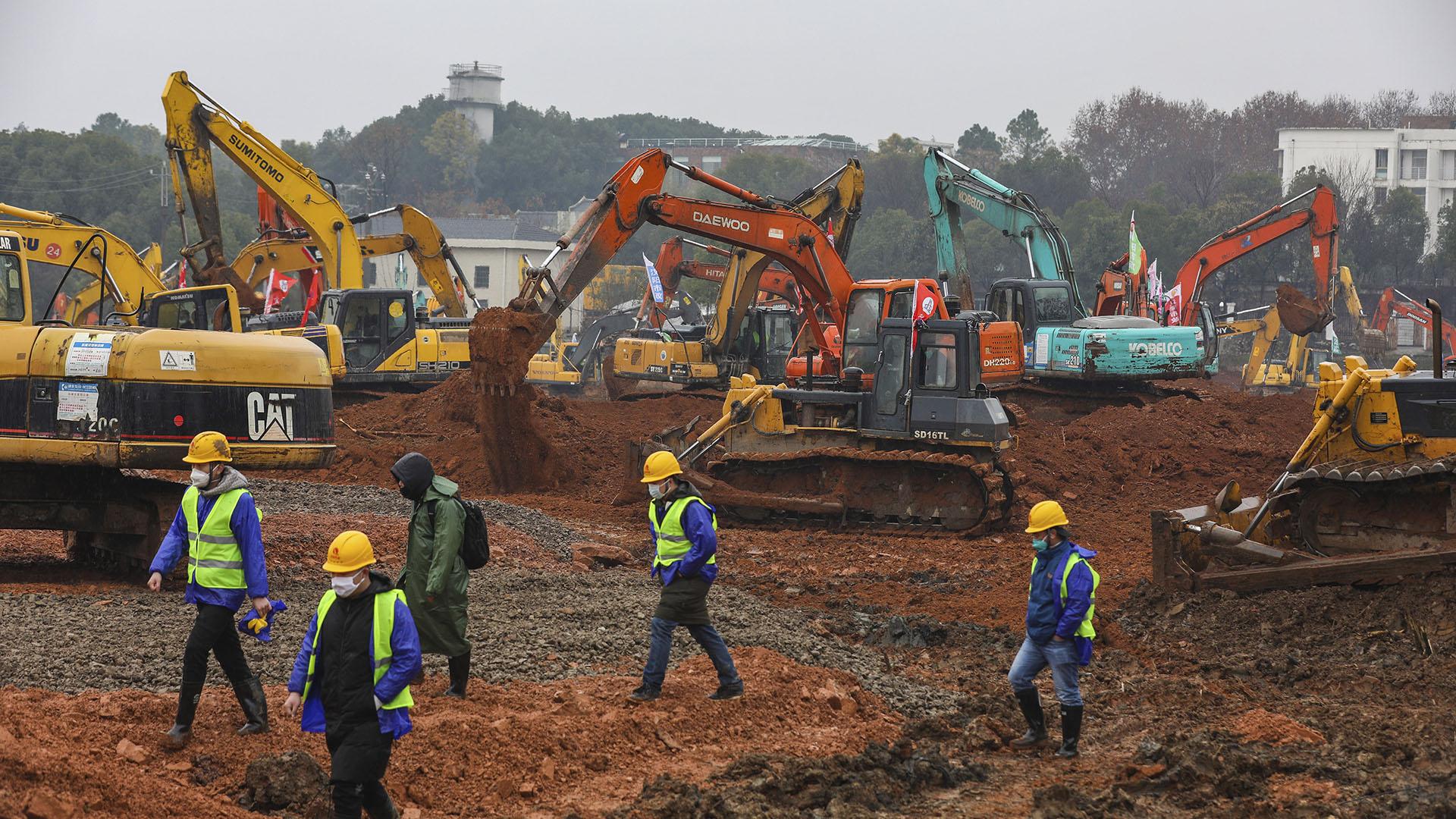 Los trabajadores pasan junto a equipos pesados en un sitio de construcción de un hospital de campaña en Wuhan, en la provincia central china de Hubei, el viernes 24 de enero de 2020. (Chinatopix a través de AP)