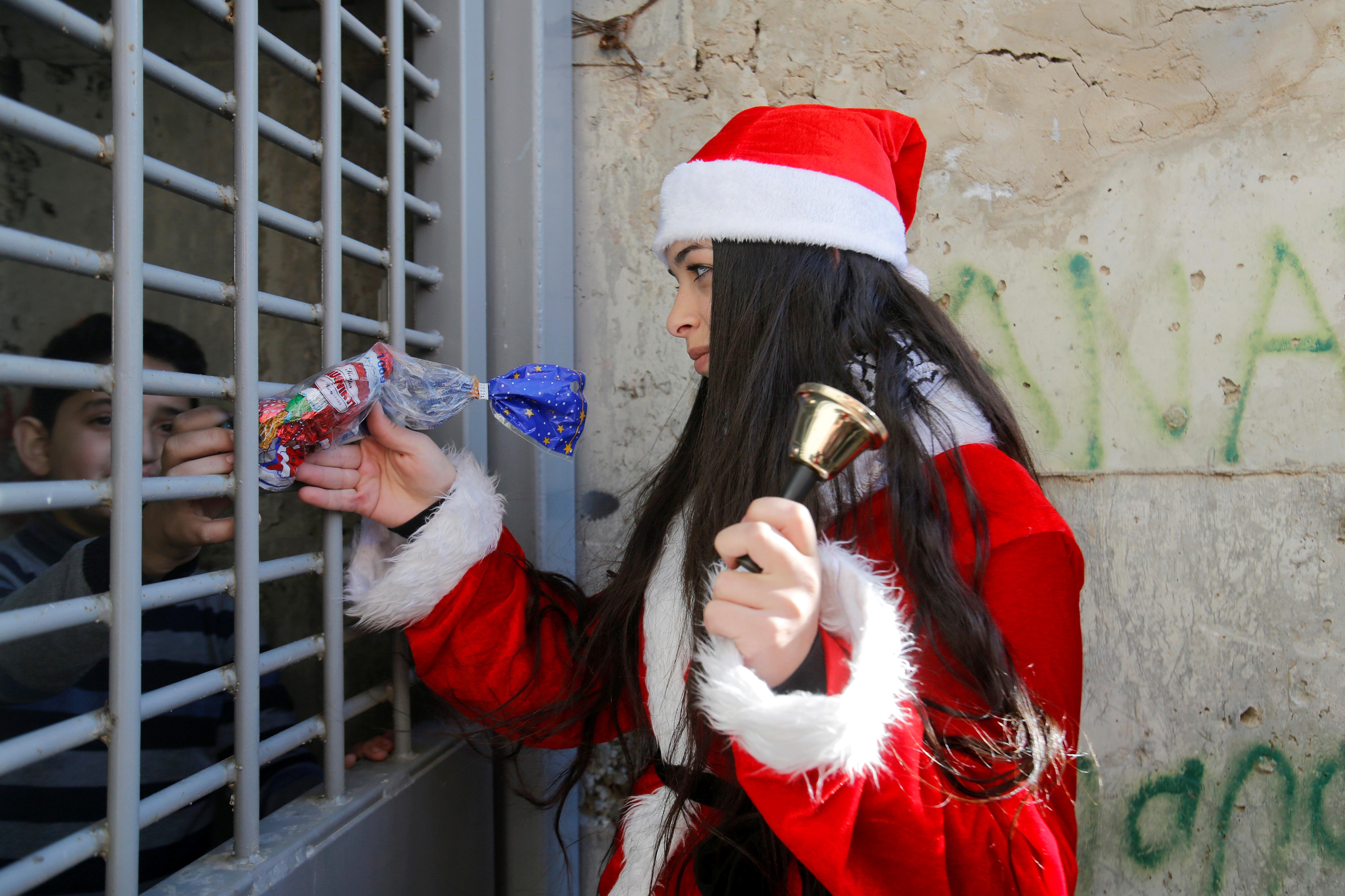 Una mujer vestida como Santa Claus le da un regalo a un niño palestino que vive al otro lado de la barrera israelí que separa Jerusalén de Cisjordania, durante una protesta contra Israel cerca de Belén el 23 de diciembre de 2019 (Reuters/ Mussa Qawasma)