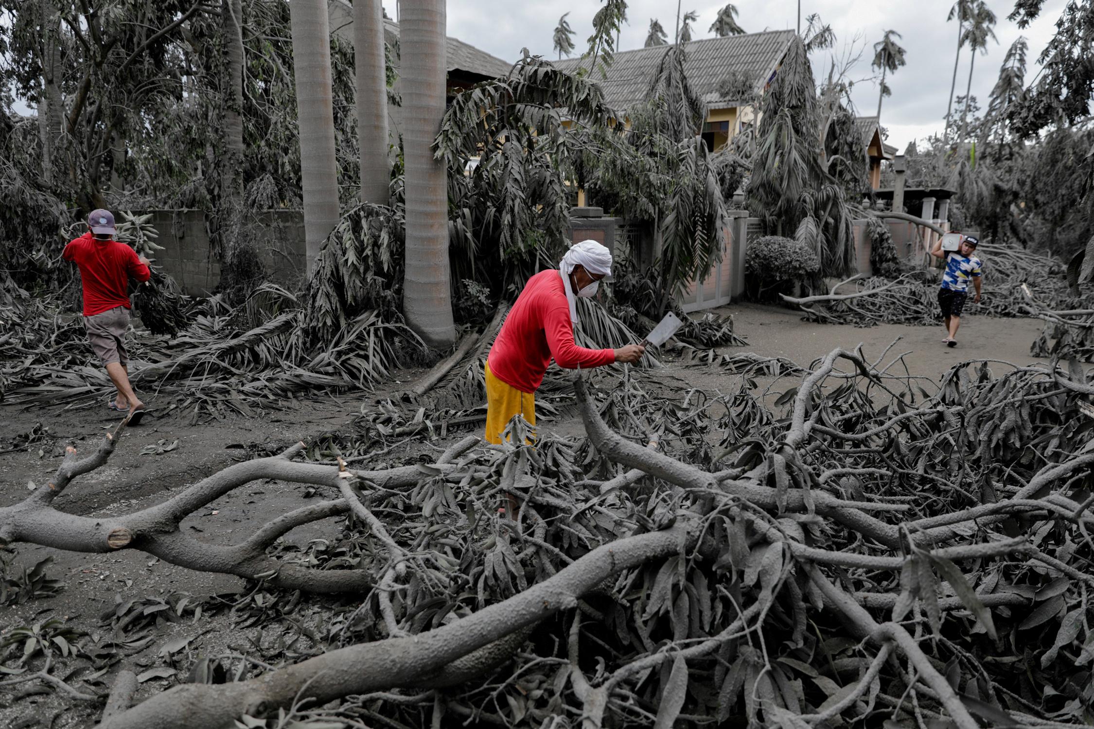 Un trabajador corta ramas caídas en un complejo cubierto de cenizas volcánicas en Talisay, Batangas, Filipinas, 14 de enero de 2020. REUTERS / Eloisa Lopez
