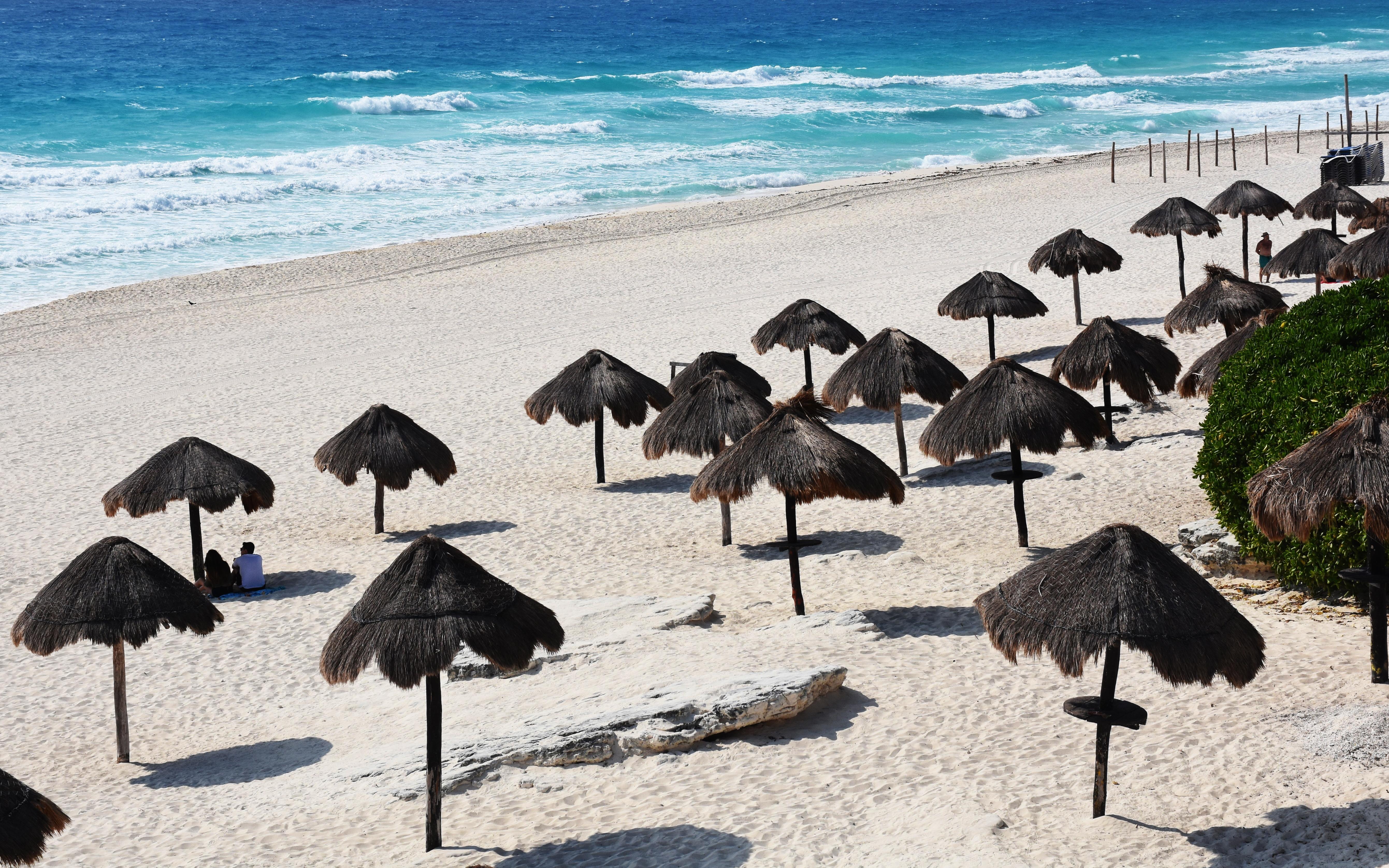 Una pareja solitaria de turistas disfruta de la playa en Cancún, estado de Quintana Roo, México, el 28 de marzo de 2020.