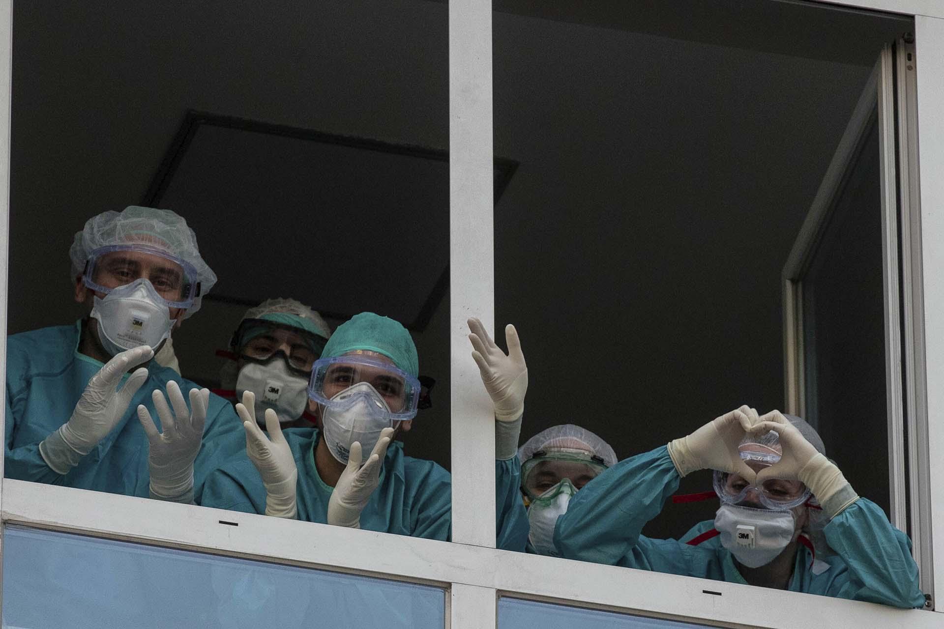 Trabajadores de la salud reaccionan a los aplausos de quienes les agradecen por su trabajo en la Fundación Universitaria Jimenez Diaz en Madrid, España (AP Photo/Manu Fernandez)