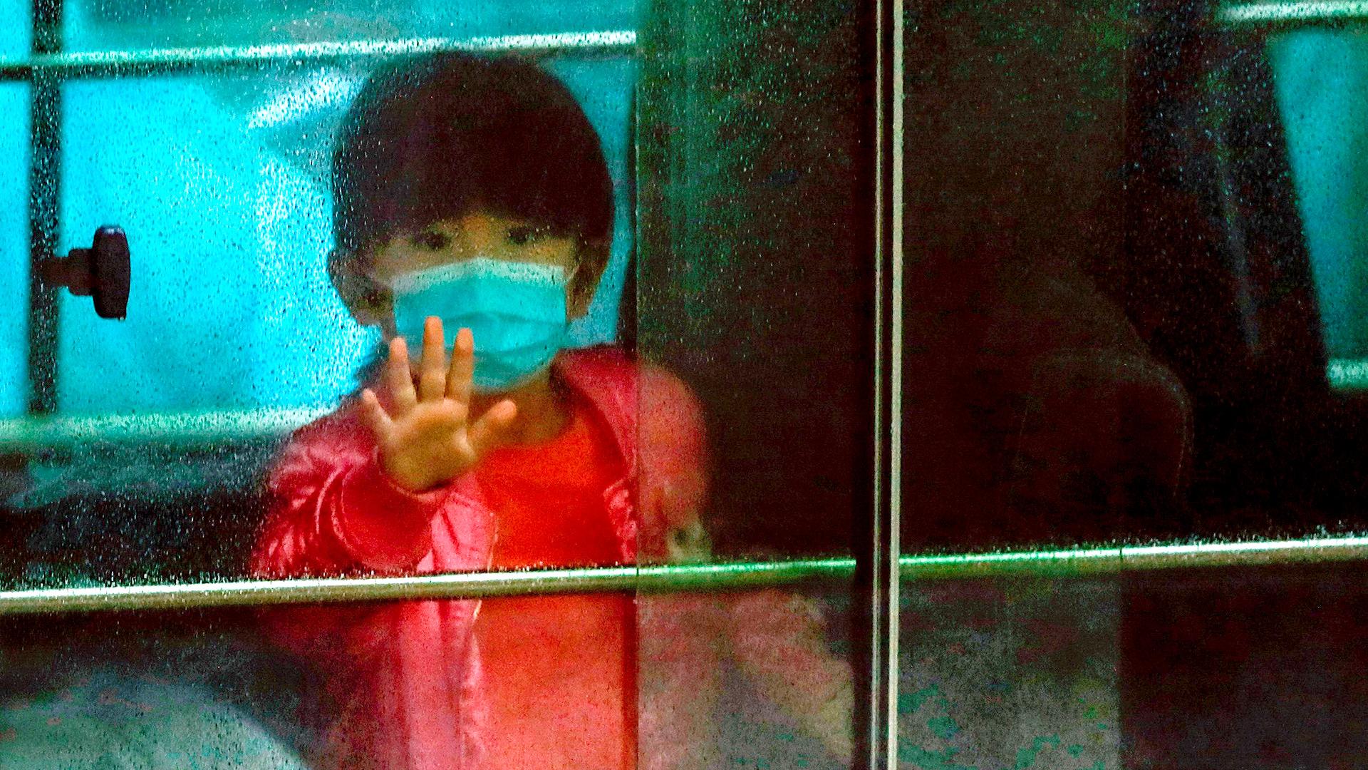 Una niña saluda mientras se sienta en un vehículo que transporta a los residentes evacuados de un edificio de viviendas públicas, en las afueras de la casa Hong Mei, en Cheung Hong Estate, en Hong Kong (REUTERS / Tyrone Siu)