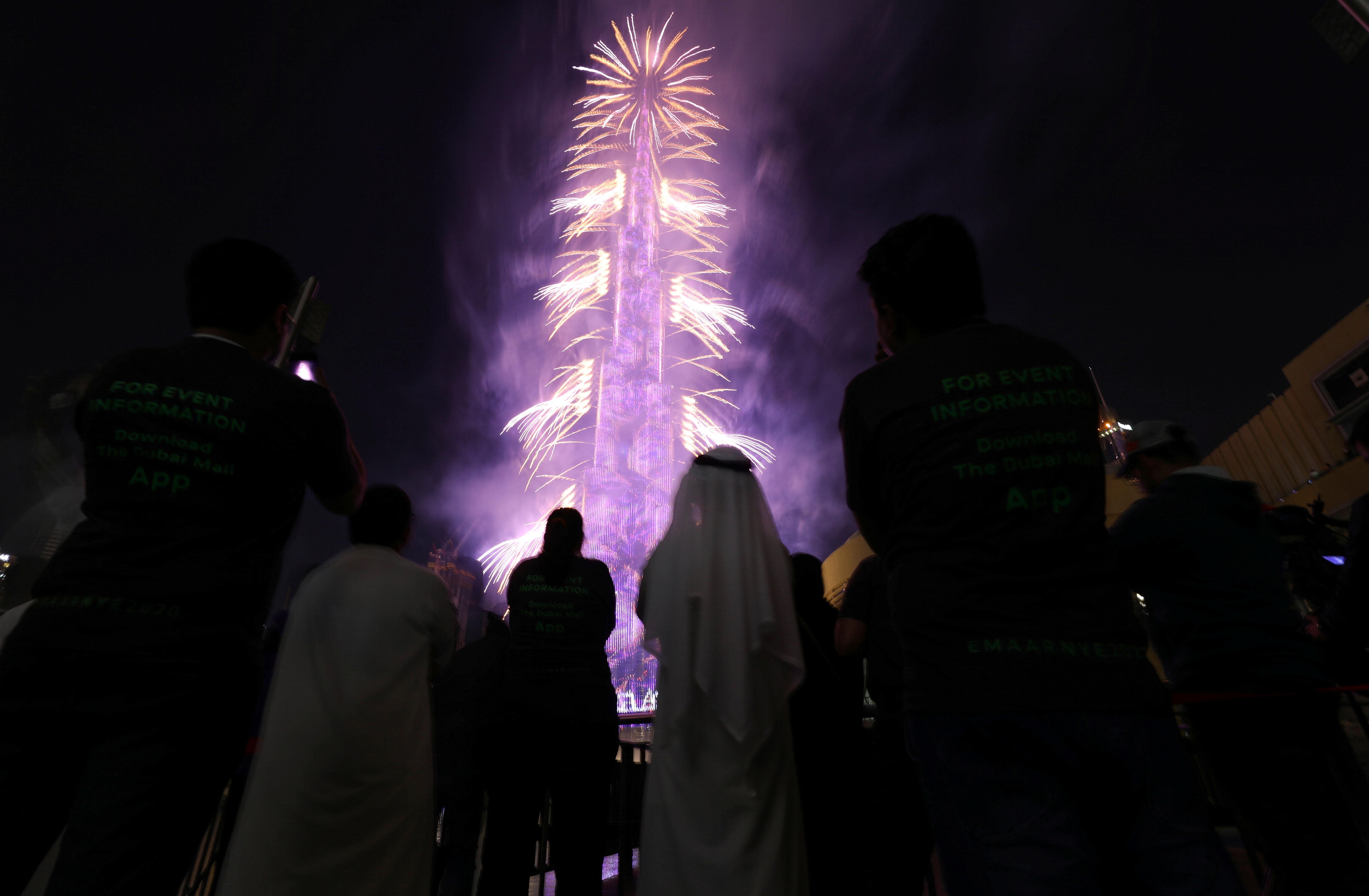 La gente ve estallar fuegos artificiales alrededor del Burj Khalifa, el edificio más alto del mundo, durante las celebraciones de Año Nuevo en Dubai, Emiratos Árabes Unidos (REUTERS/Christopher Pike)