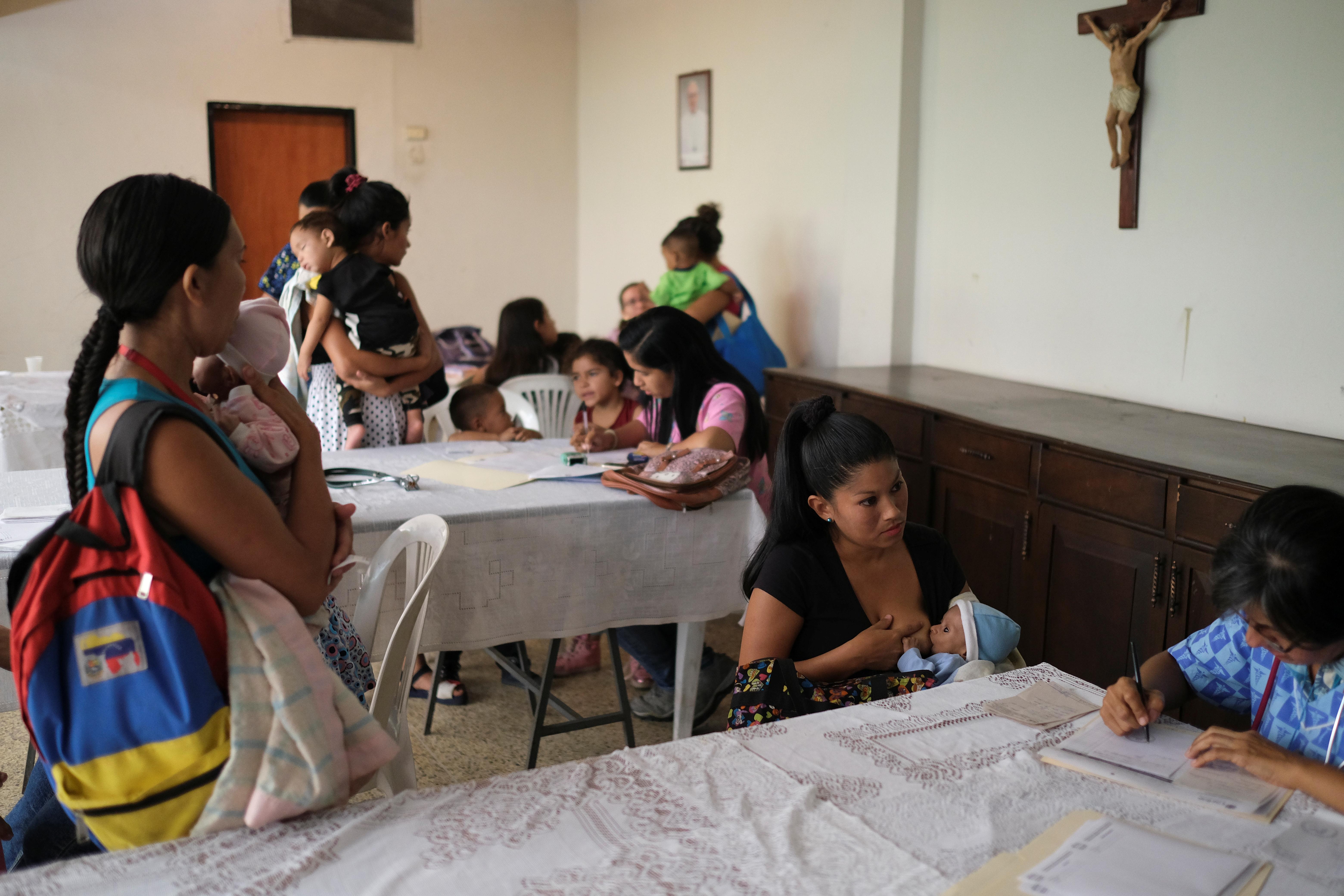 Distintas familias con niños desnutridos asisten a un encuentro en una iglesia (REUTERS/Carlos García Rawlins)