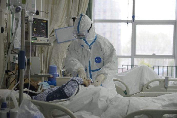 Un médico cubierto para evitar el contagio atiende a un paciente en el hospital de Wuhan (vía REUTERS)