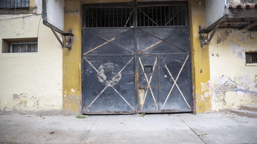 Una puerta de doble hoja ya azulada por el tiempo sobre calle Pichincha es el acceso principal. Todavía quedan los contornos de los escudos en los que hasta hace poco se leía: