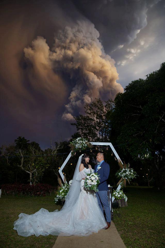 Una pareja celebra a su ceremonia de boda mientras Taal Volcano envía una columna de cenizas en el fondo en Alfonso, Cavite, Filipinas, el 12 de enero de 2020. Randolf Evan Photography / REUTERS.