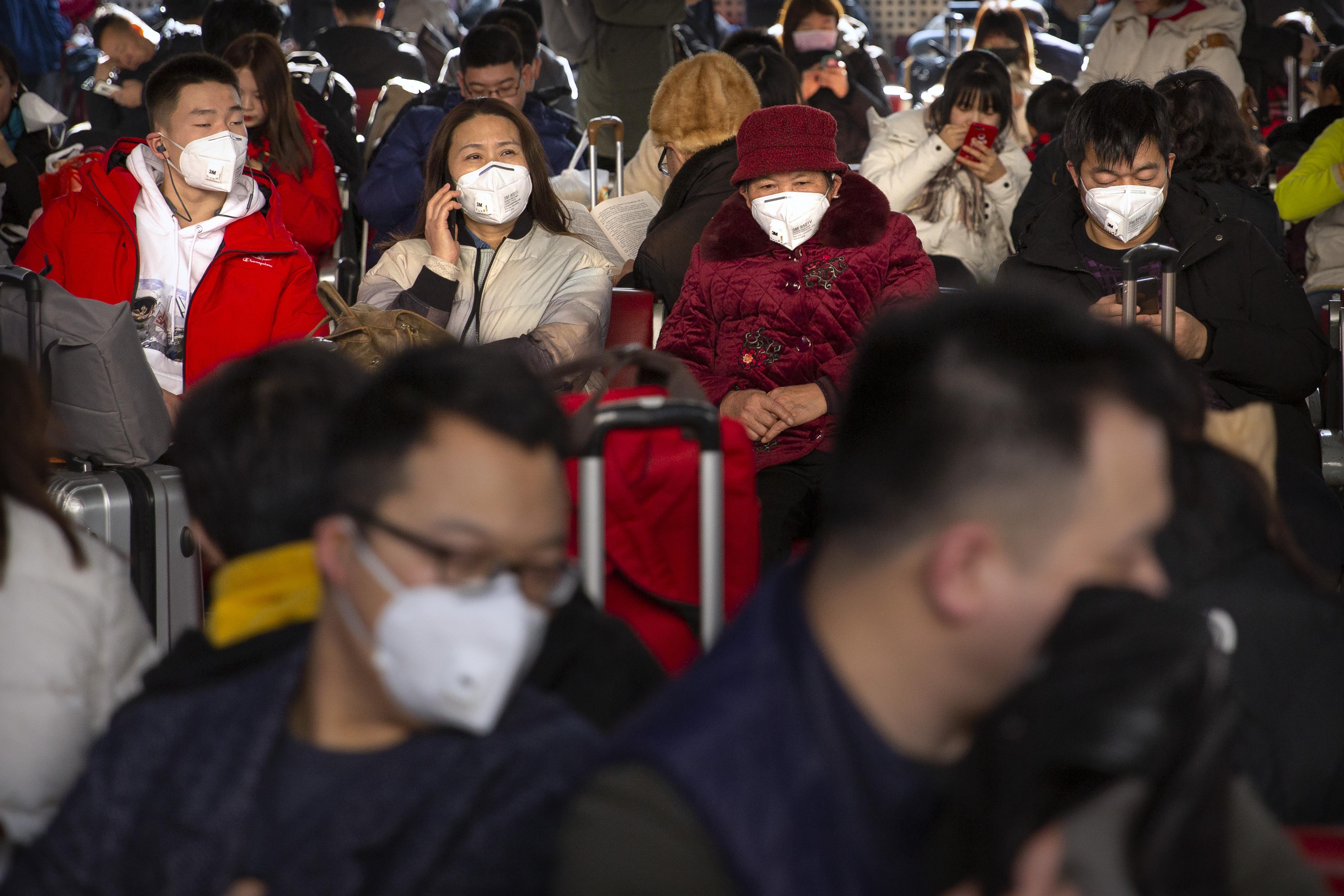 Los viajeros usan máscaras faciales mientras se sientan en una sala de espera en la Estación de Ferrocarril Oeste de Beijing en Beijing, el martes 21 de enero de 2020. Una cuarta persona murió en un brote de un nuevo coronavirus en China, dijeron las autoridades el martes. intensificó el examen médico de los viajeros del país a medida que entra en su período de mayor actividad. (Foto AP / Mark Schiefelbein)