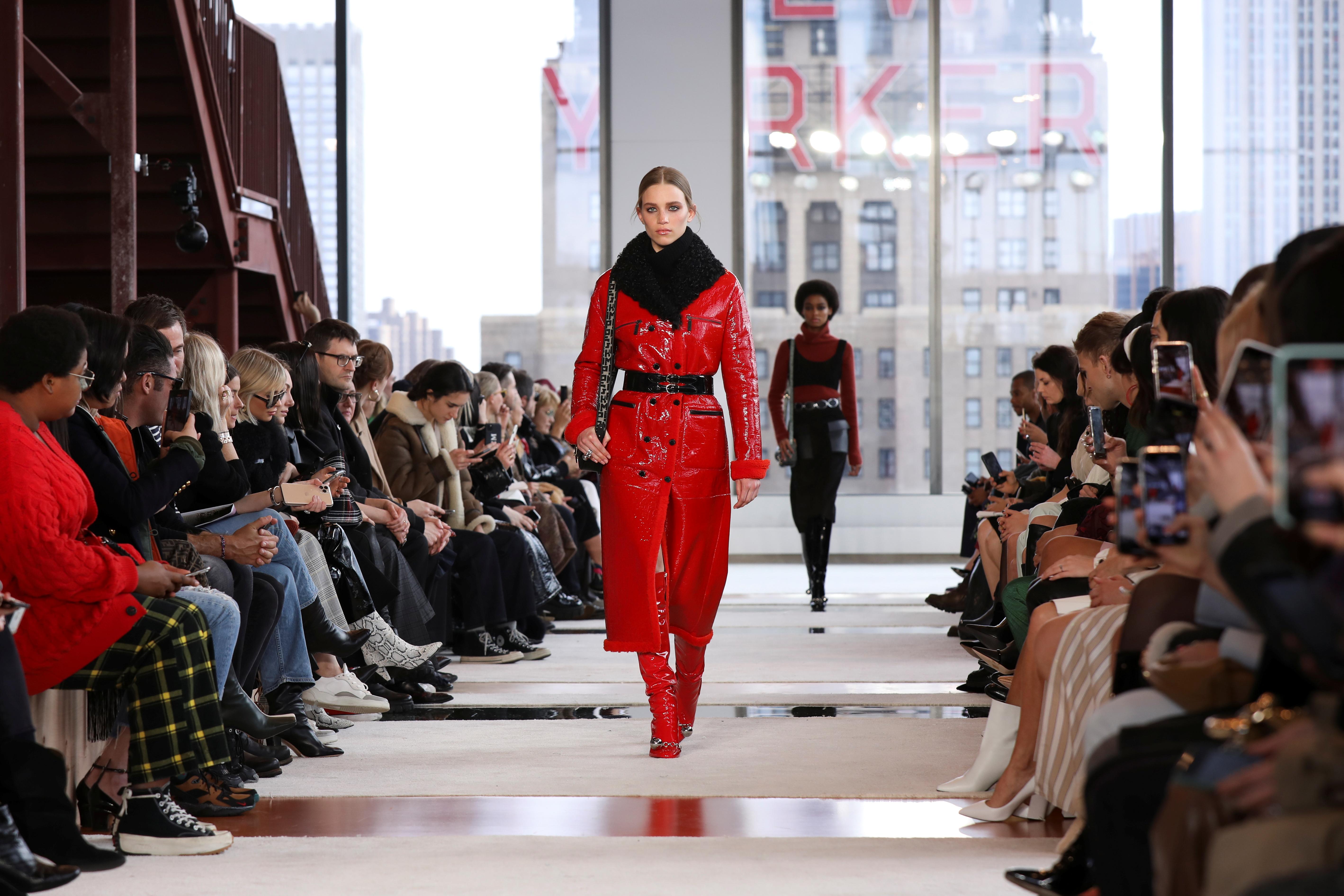 La modelo Rebecca Longendyke desfilando para Longchamp lució un abrigo rojo de vinilo de largo midi, con botas a tono, cinturón de cuero negro y cuello de piel negro. ¿De accesorio? La cartera con correa de logotipo
