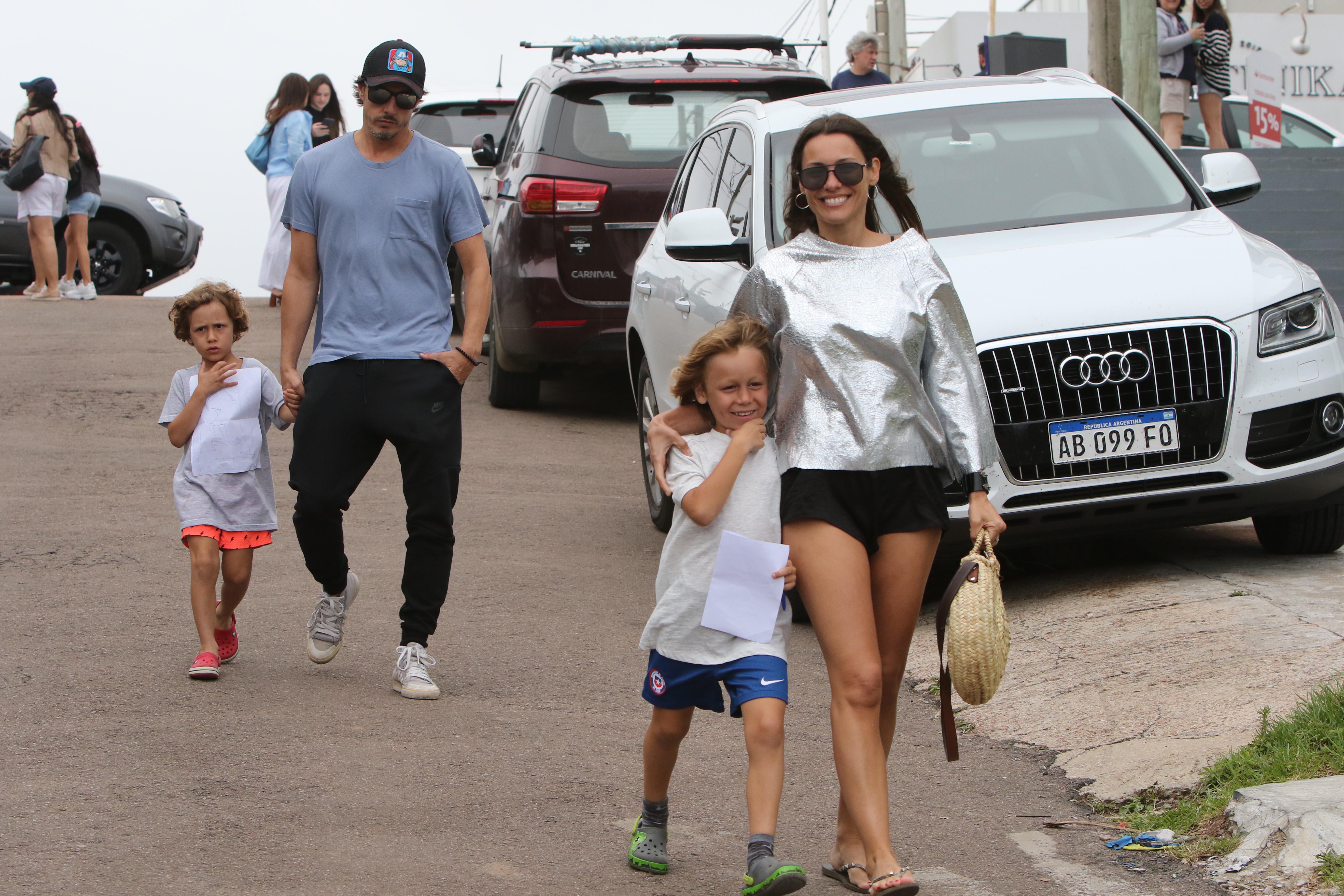 Un buzo metalizado, short negro y cartera de rafia para un paseo en familia en un día nublado