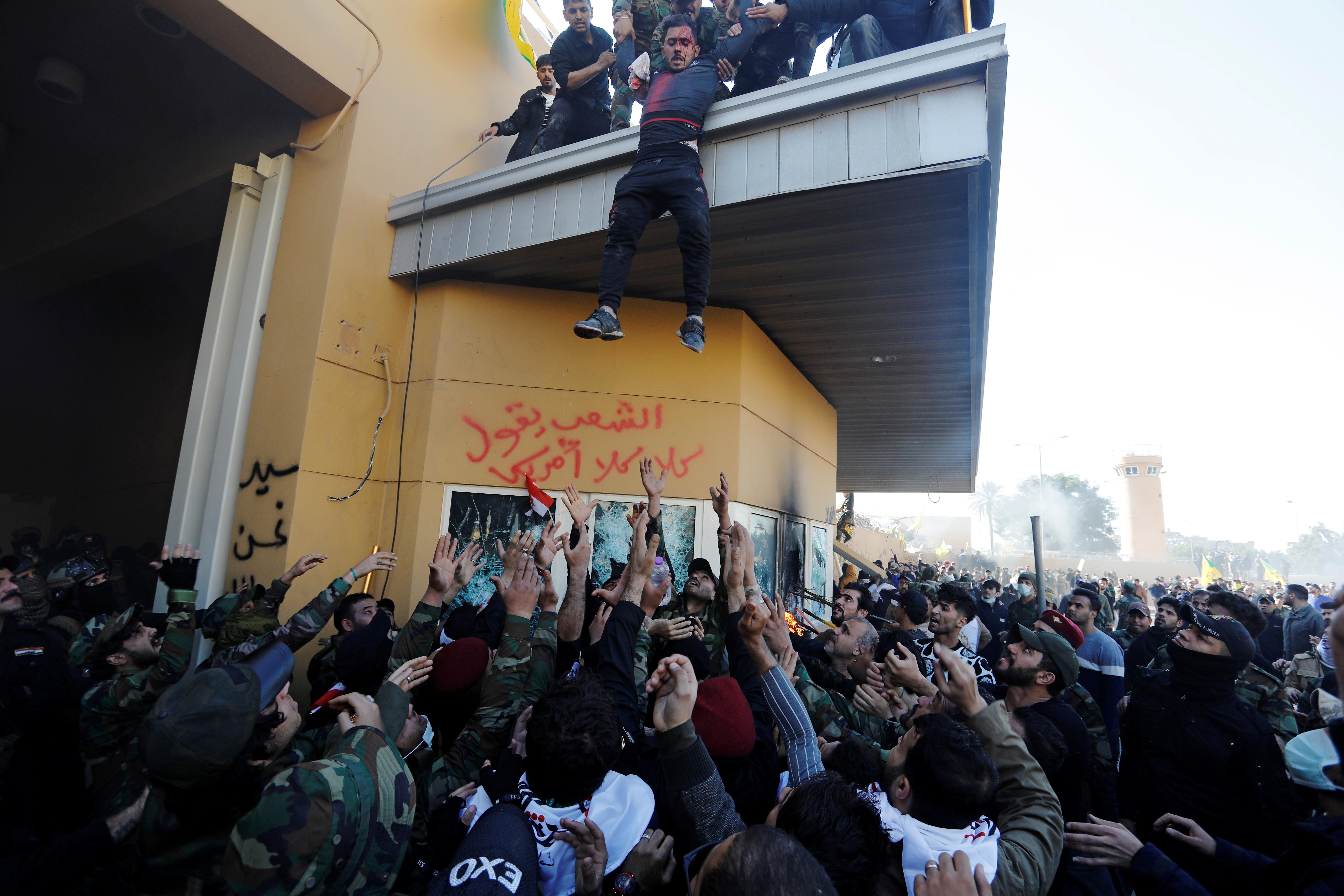 Un miliciano herido es arrojado a una multitud que espera para trasladarlo