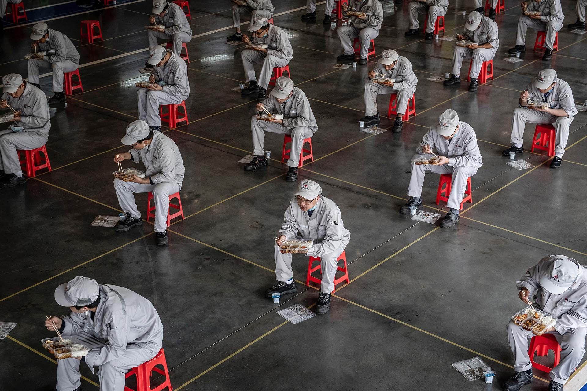Empleados a la hora del almuerzo en una fábrica de automoviles, Honda, en Wuhan, donde comenzó la pandemia y esta semana fueron autorizados a regresar a sus trabajos.