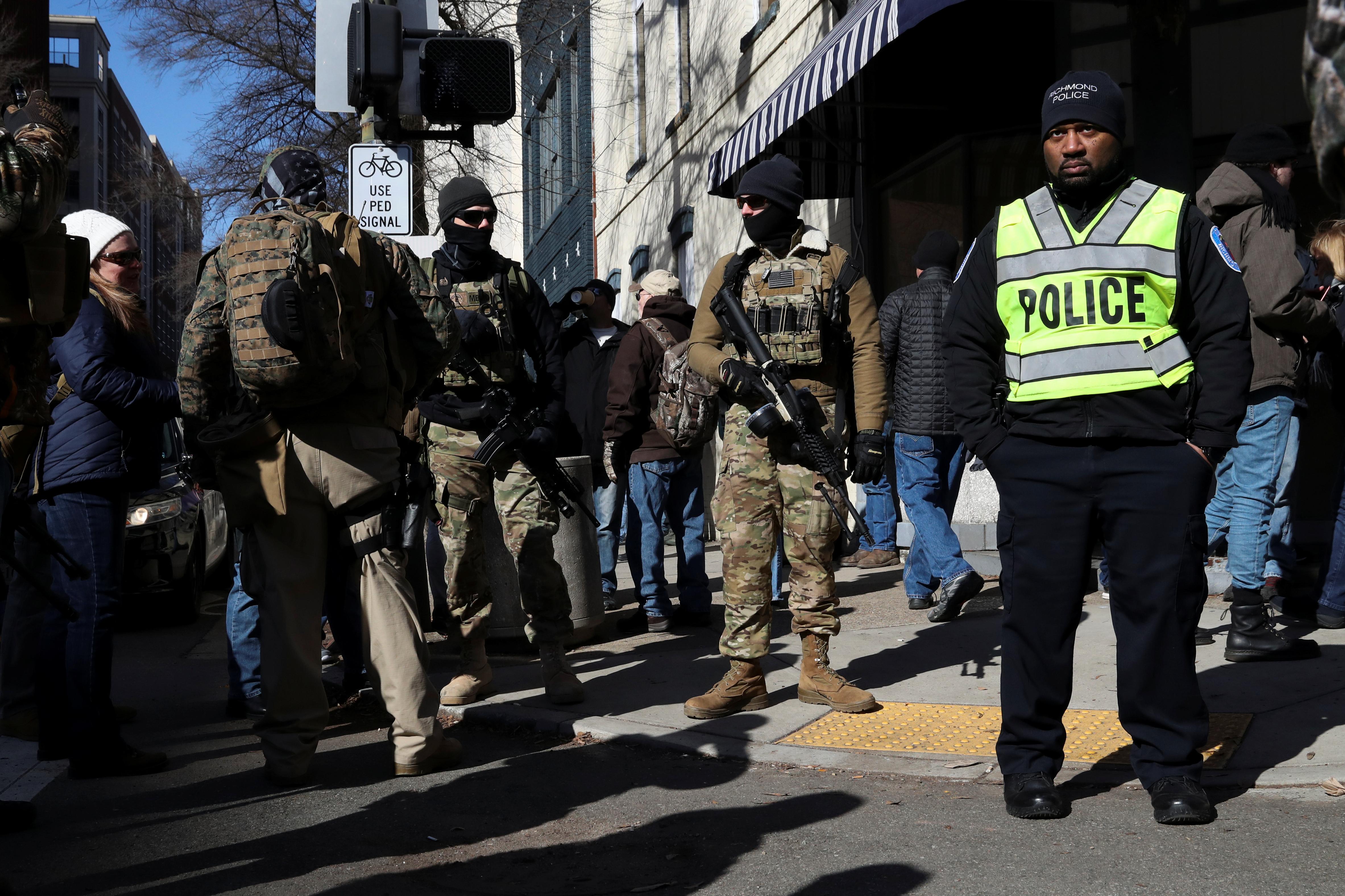 Tres hombres fuertemente armados, junto a un policía, desarmado (REUTERS/Leah Millis)