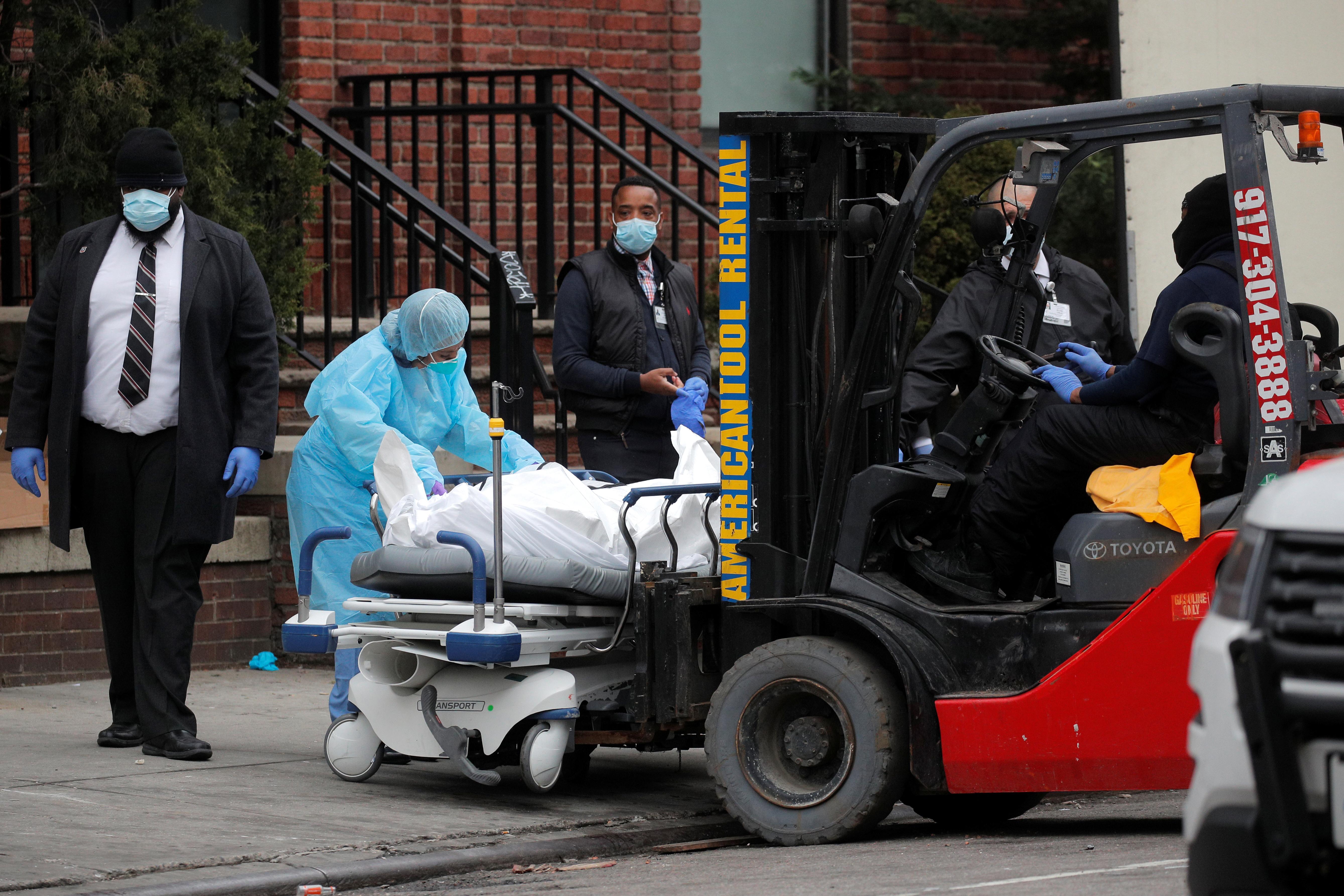 Un grupo de trabajadores se prepara para cargar a una persona fallecida en un remolque afuera del Centro Hospitalario de Brooklyn, Nueva York (REUTERS/Brendan Mcdermid)