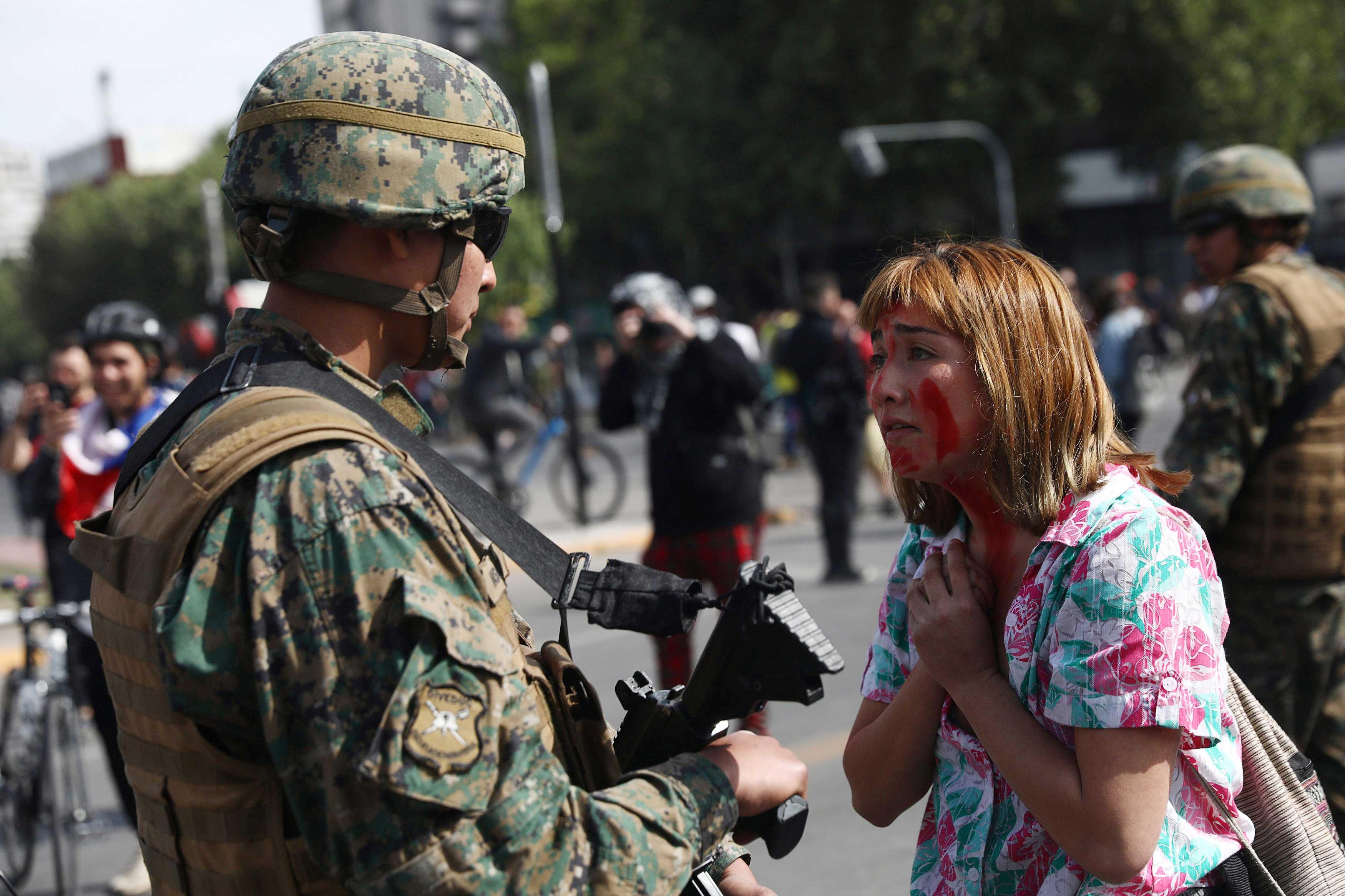Una manifestantes dialoga con un soldado en la calles de la capital chilena