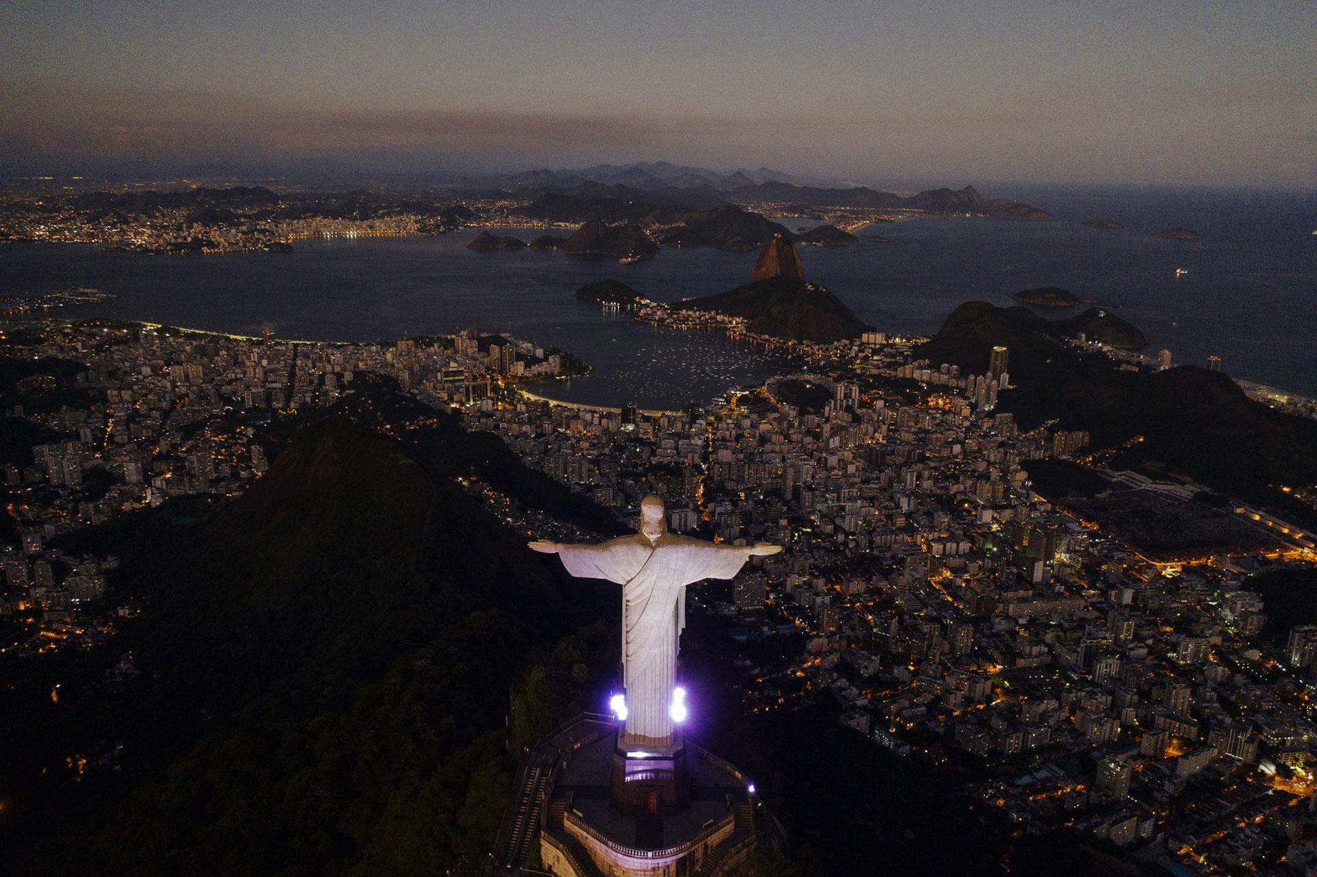 La estatua del Cristo Redentor se alza sobre la bahía de Guanabara durante el anochecer en medio del brote del coronavirus en Río de Janeiro, Brasil, el lunes 27 de abril de 2020. (Foto AP / Leo Correa)