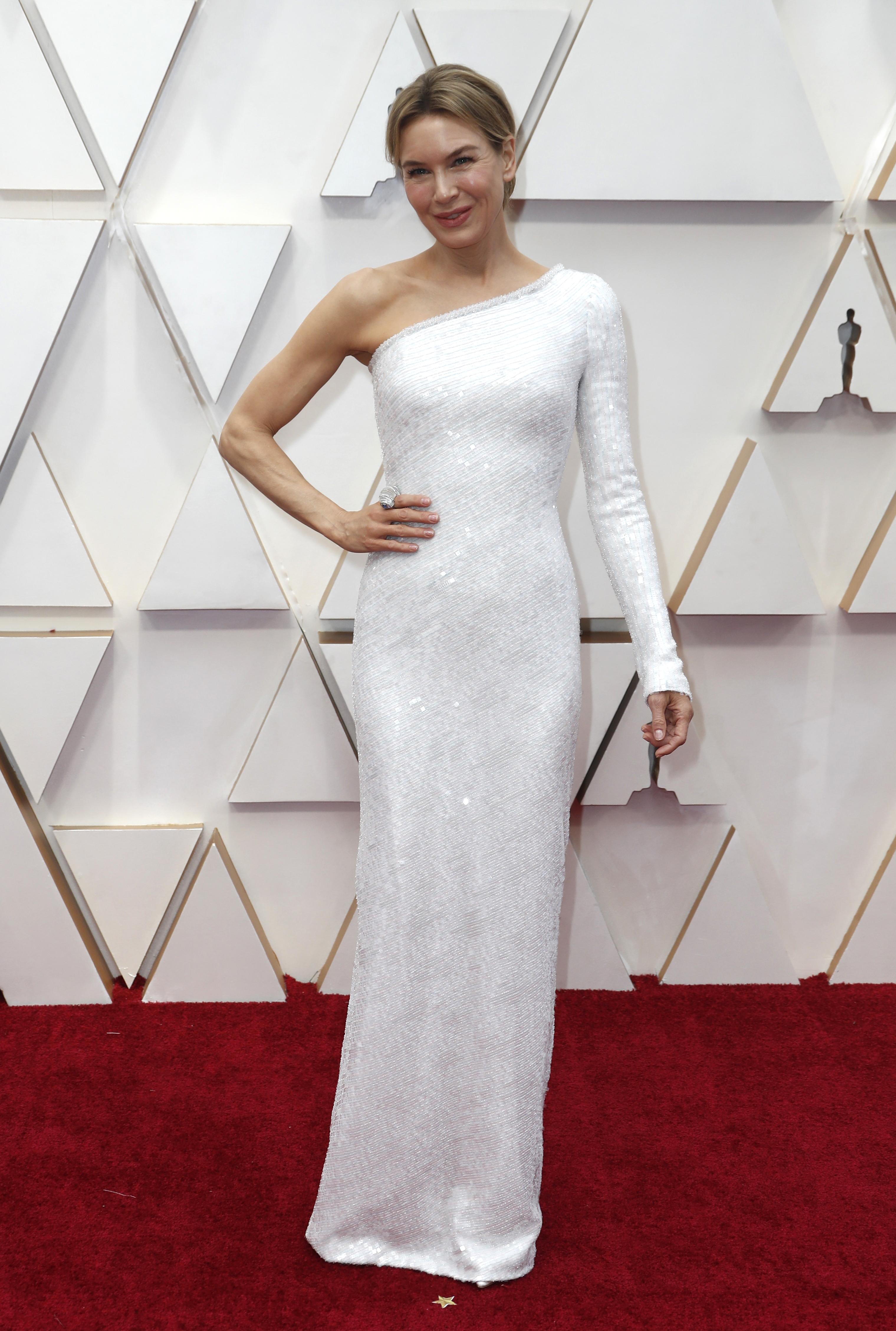 Renee Zellweger lució un vestido con una sola manga en blanco, de paillettes con silueta sirena. Completo su look con un anillo plateado y para su beauty look, optó por un peinado recogido y maquillaje al natural