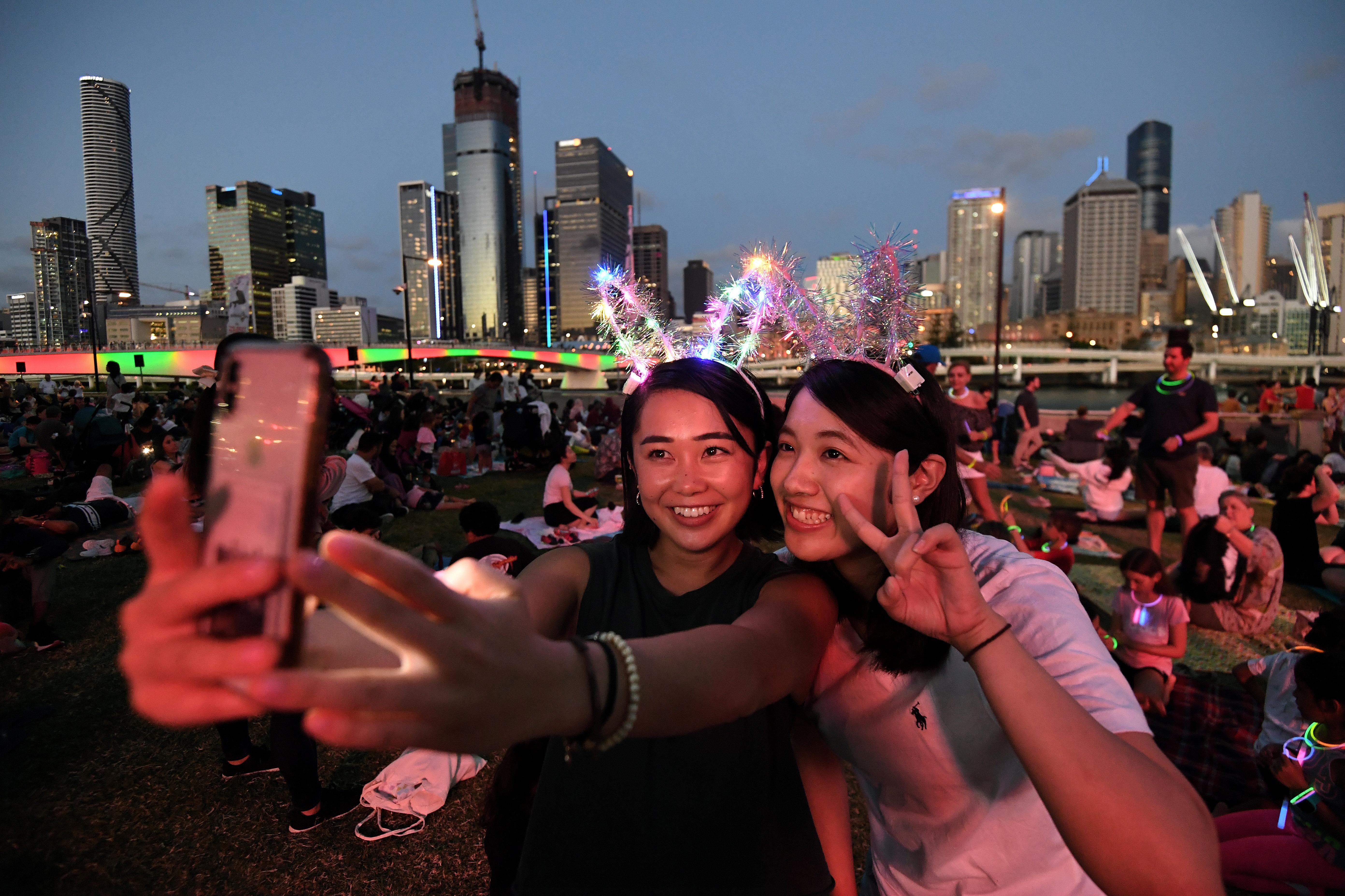Dos mujeres esperan el show de fuegos artificiales frente a la bahía de Brisbane en Australia
