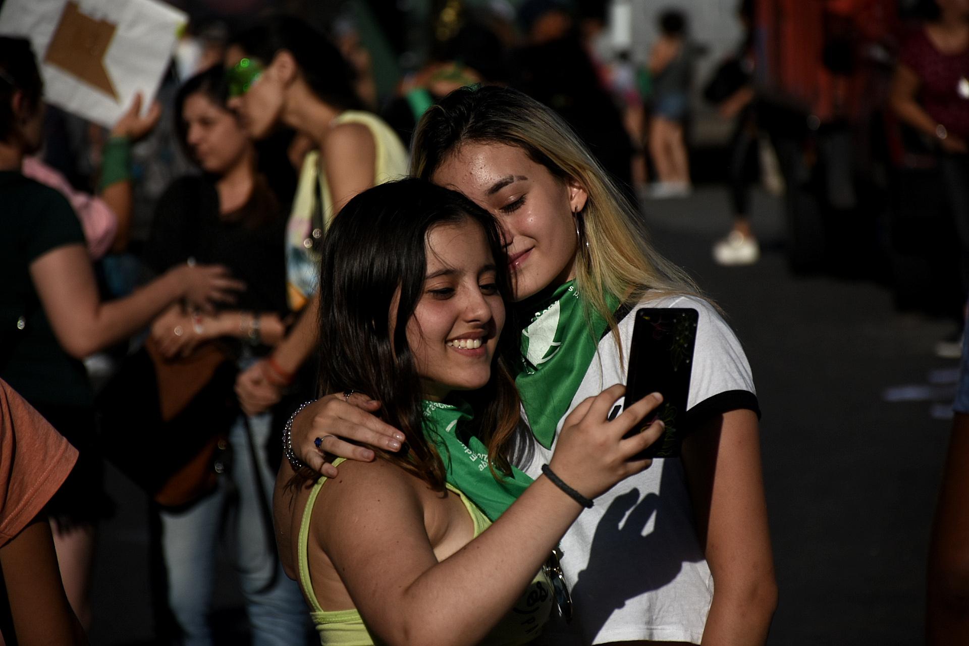 Dos jóvenes posan para una selfie con el pañuelo verde