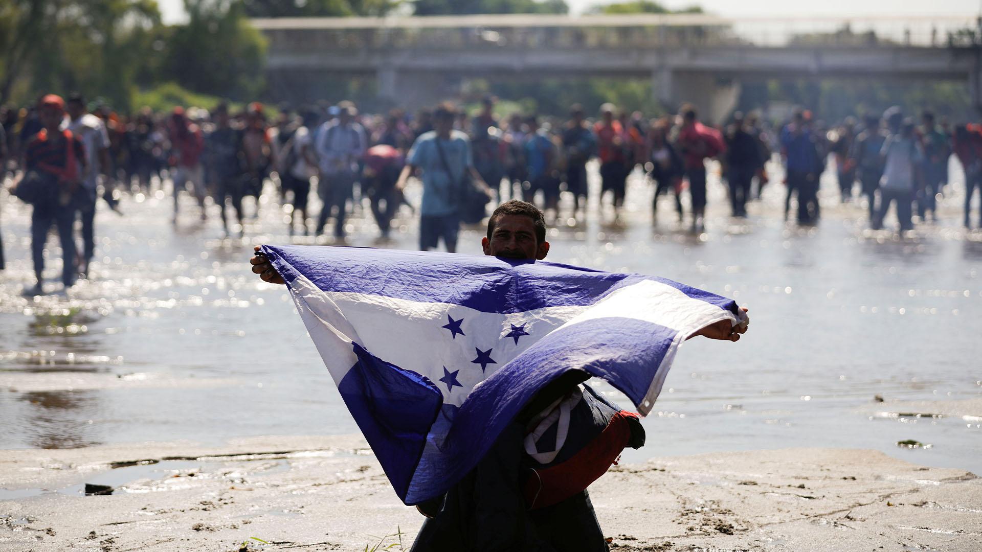 Un inmigrante sostiene la bandera de Honduras mientras intentan cruzar por la fuerza la frontera de México con este país (Foto: José Cabezas/Reuters)