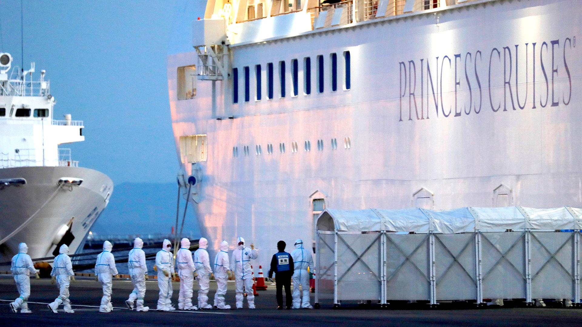 Oficiales con equipo de protección ingresan al crucero Diamond Princess para trasladar a un paciente al hospital después de que el barco llegara a la Terminal de Cruceros del muelle Daikoku en Yokohama, al sur de Tokio (REUTERS / Kim Kyung-Hoon)