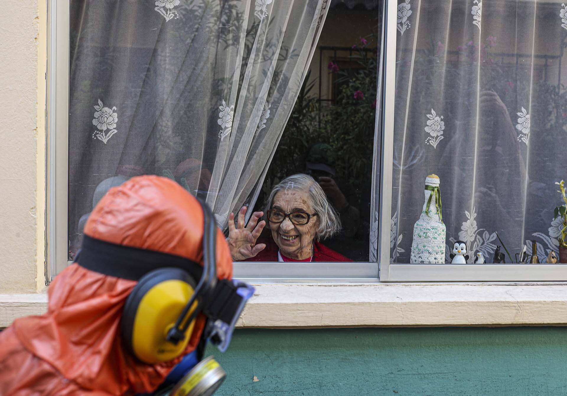 Una mujer saluda y sonríe a un trabajador vestido en un traje especial mientras desinfecta las calles de Santiago, Chile (AP Photo/Esteban Felix)