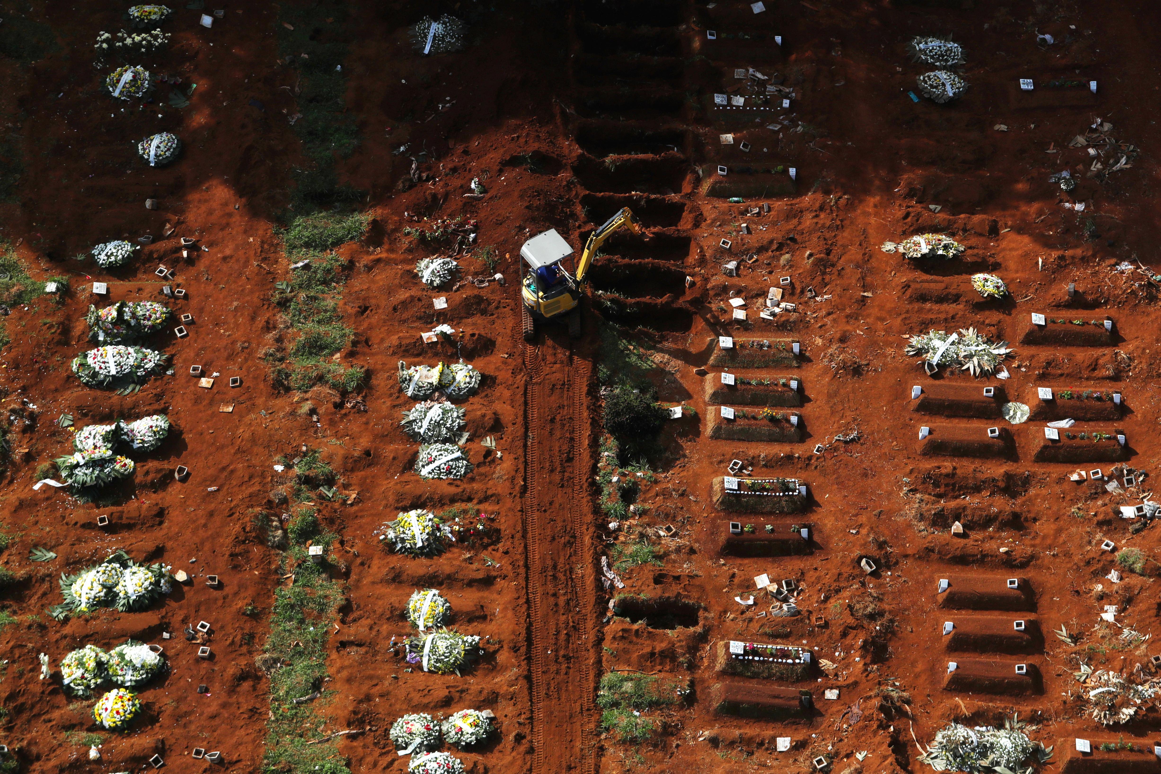 Un sepulturero abre nuevas tumbas con una excavadora a medida que aumenta el número de muertos después del brote de la enfermedad por coronavirus (Reuters)