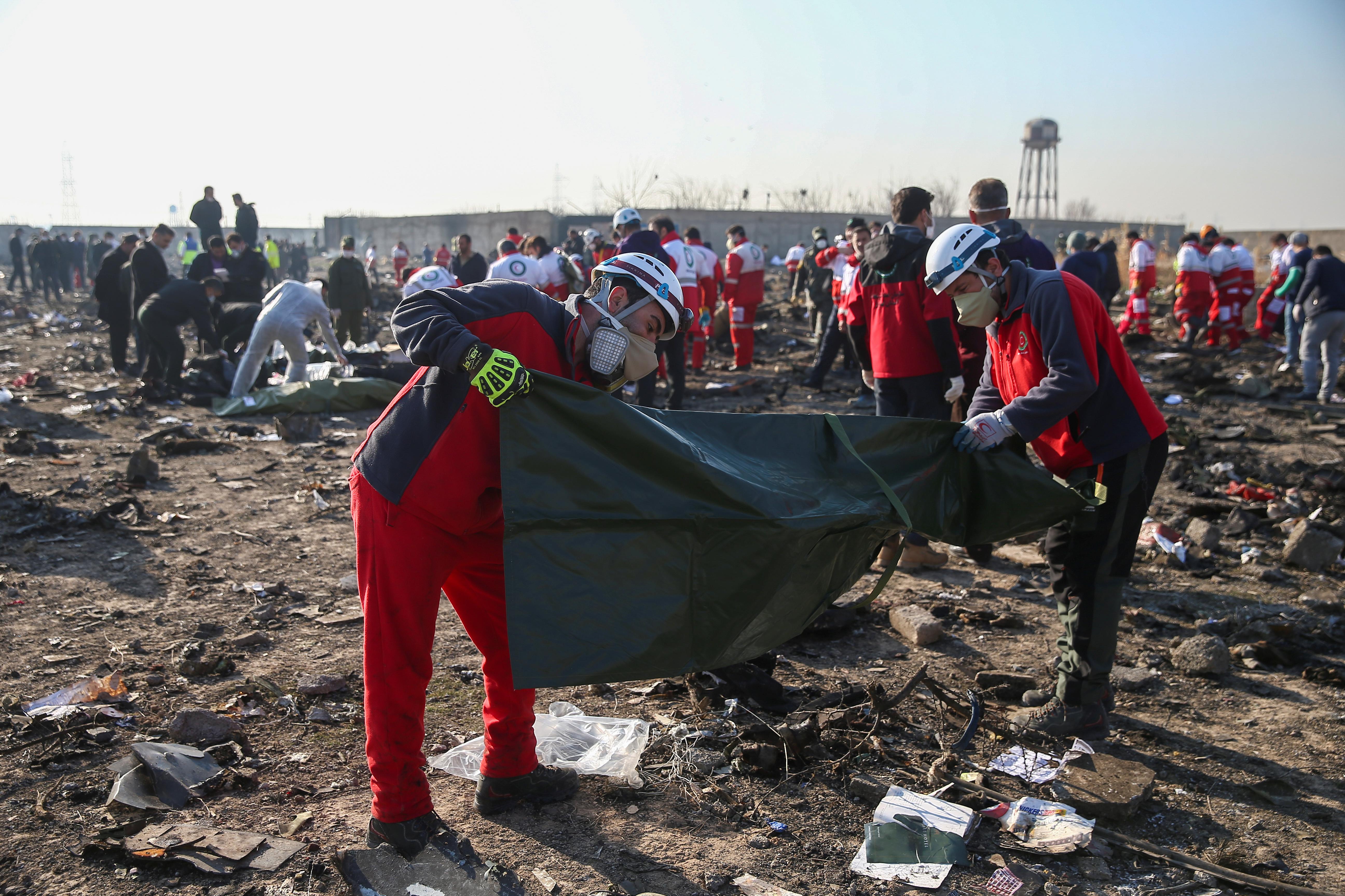 Dos socorristas preparan bolsas para colocar los cuerpos de las personas fallecidas (REUTERS)