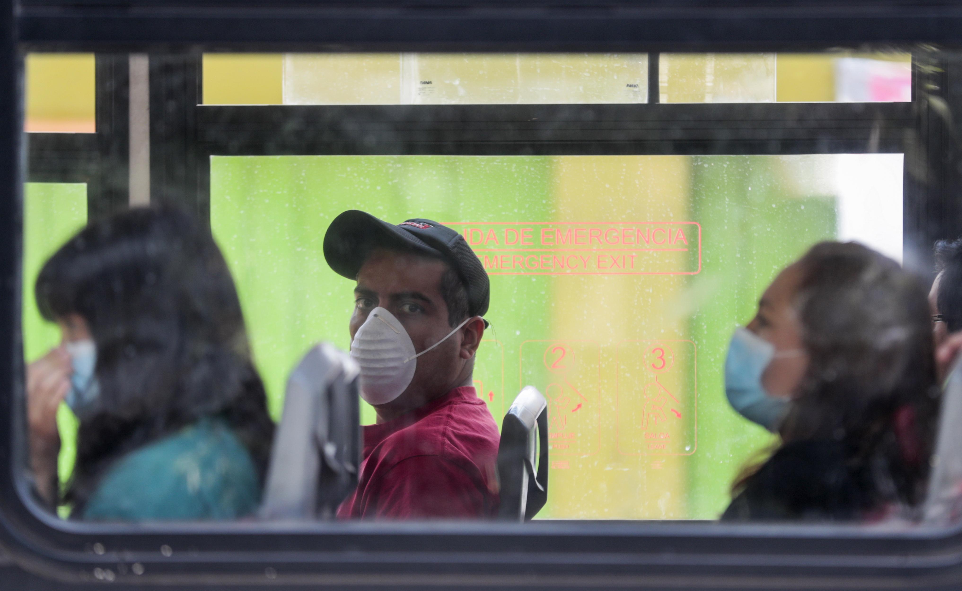 Los viajeros usan máscaras mientras viajan en un autobús, para evitar la propagación del nuevo coronavirus en la Ciudad de México, el martes 31 de marzo de 2020.