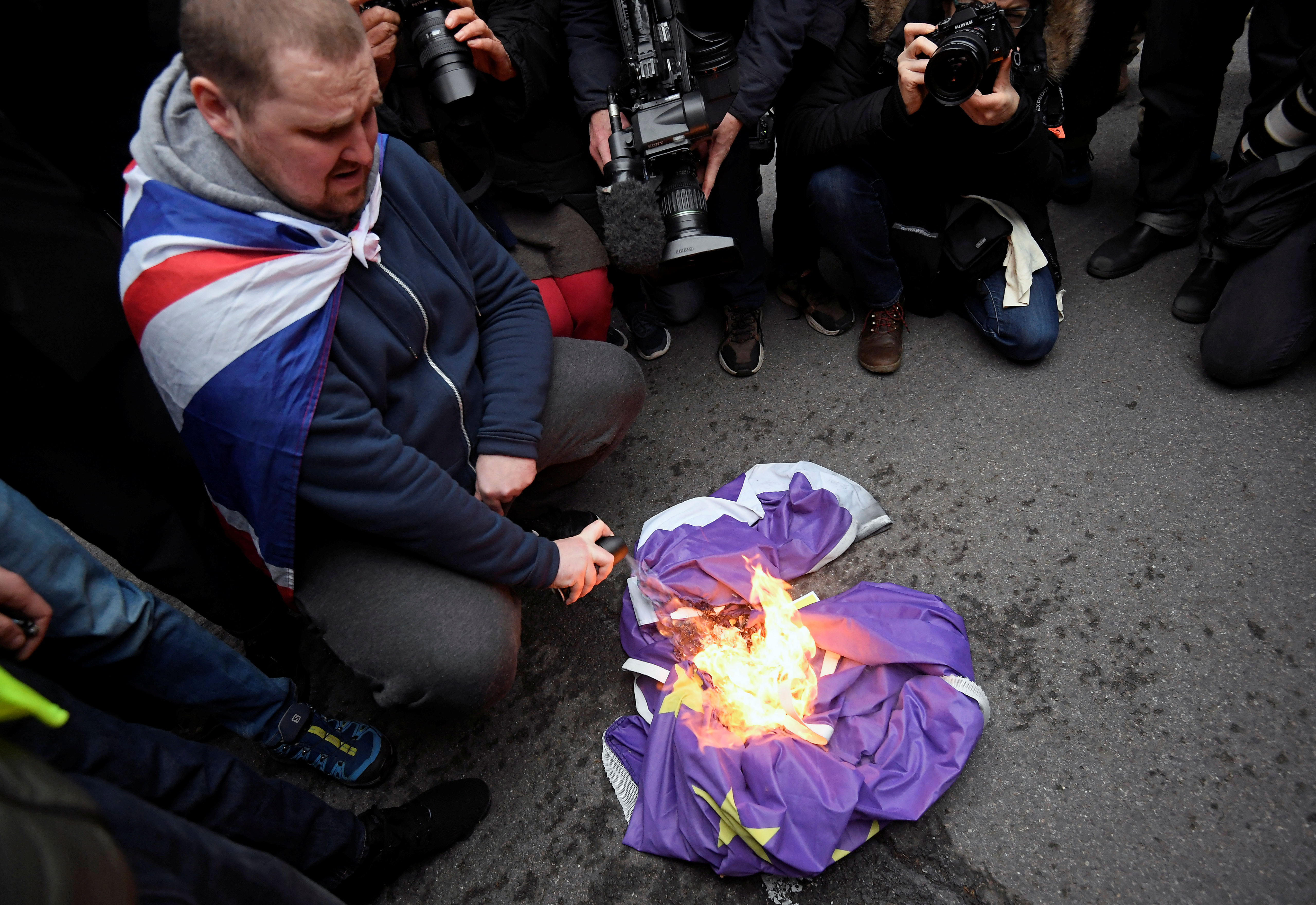 A man burns an EU flag on Brexit day in London, Britain January 31, 2020. REUTERS/Toby Melville