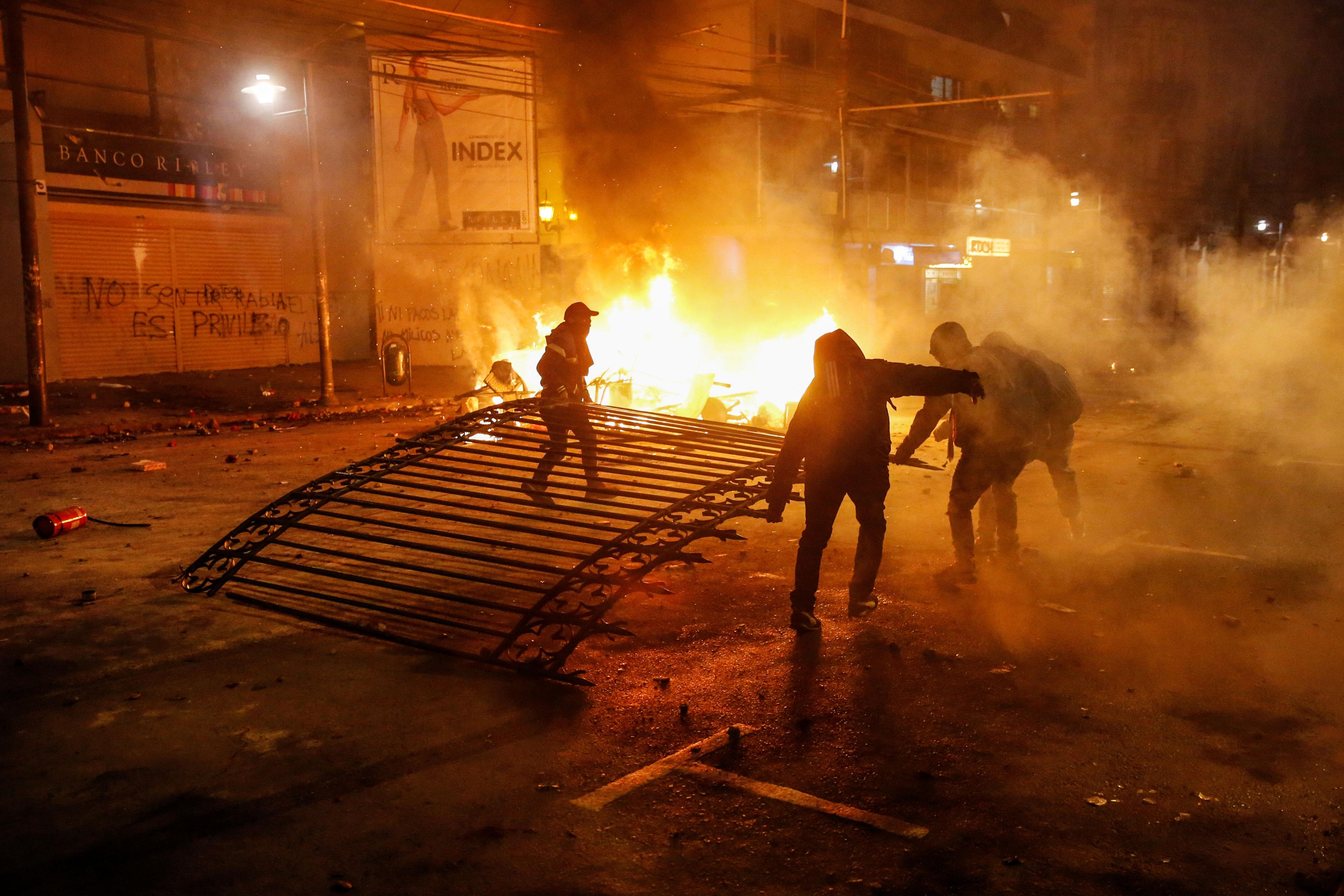 Manifestantes se llevan la puerta de hierro en la entrada de El Mercurio, el periódico más antiguo de Chile.
