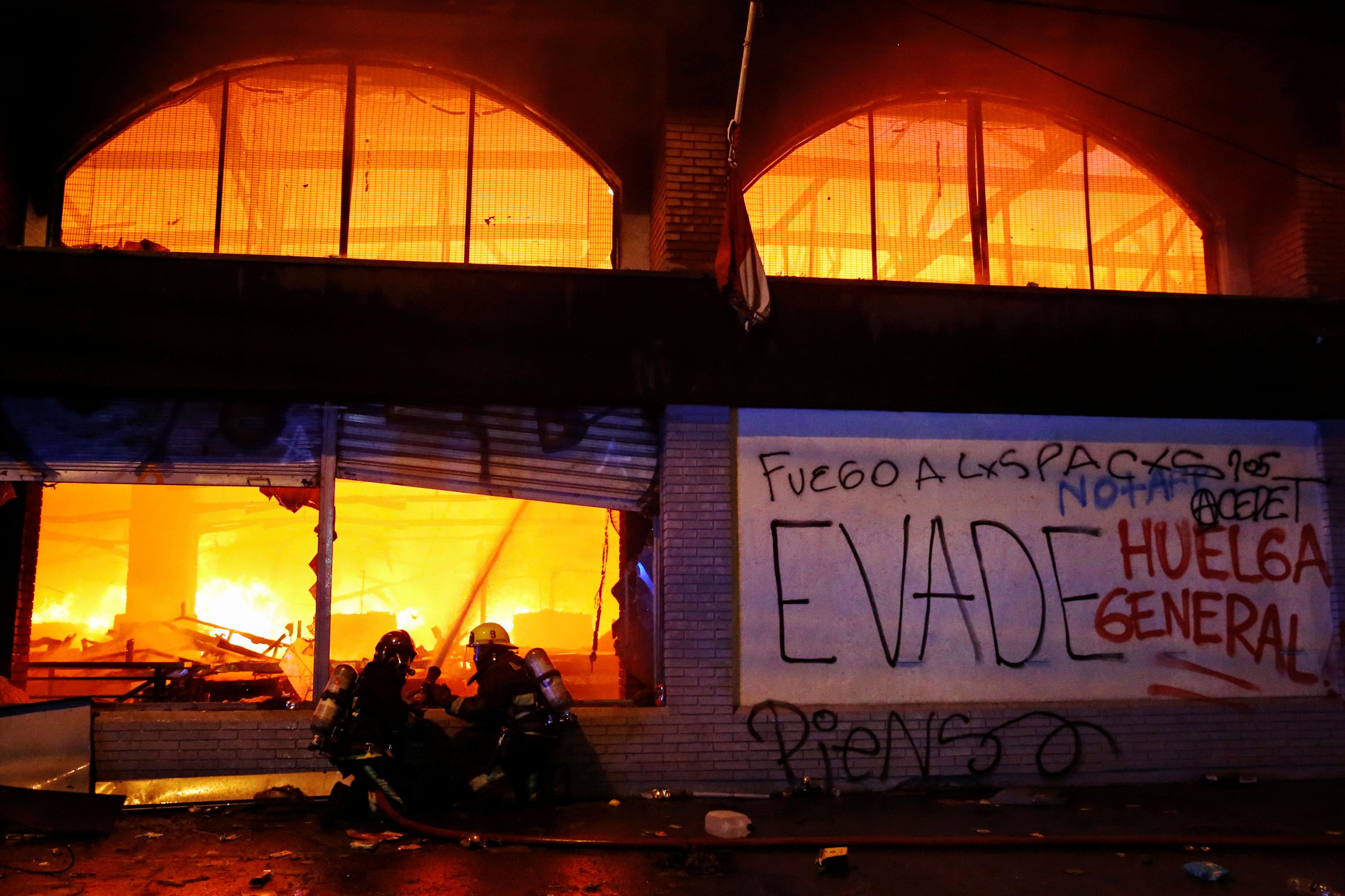 Bomberos combatiendo fuego dentro de una tienda en Santiago, Chile.
