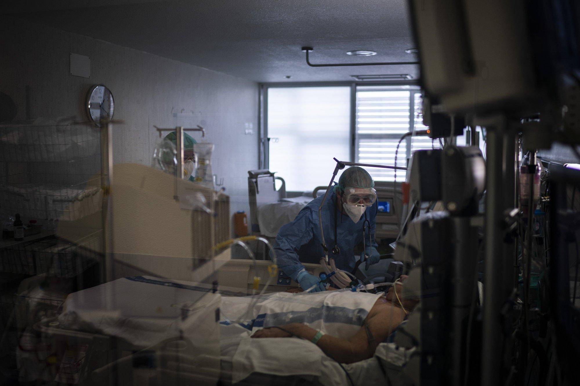 Los trabajadores de la salud ayudan a un paciente COVID-19 en una de las unidades de cuidados intensivos (UCI) (AP Photo/Felipe Dana)