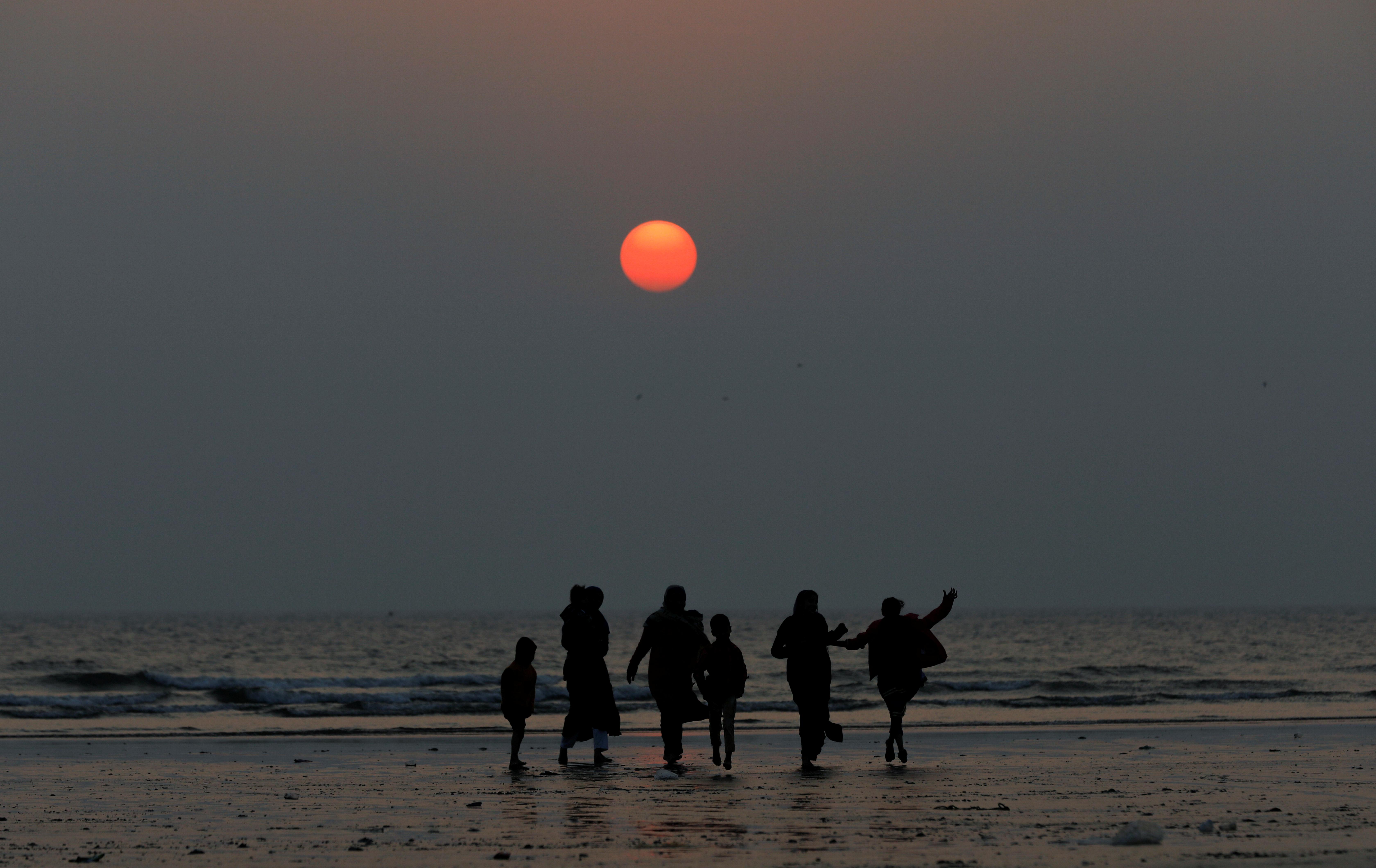 Una familia en la playa de Clifton, en Karachi, Pakistán, en la última puesta de sol de 2019