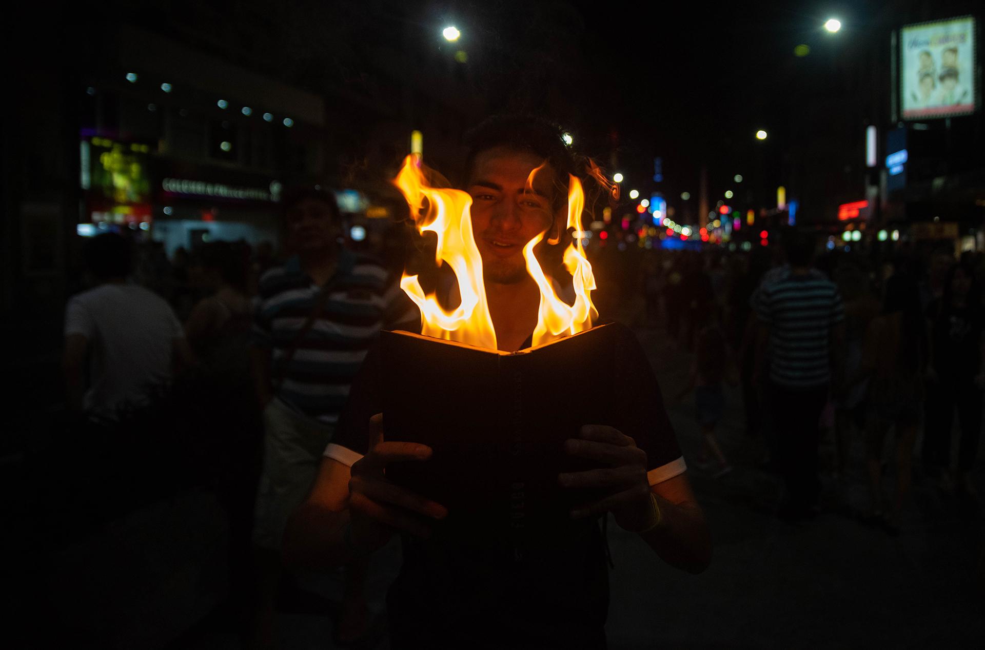 Una de las expresiones artísticas de la noche: un joven leyendo un libro en llamas.