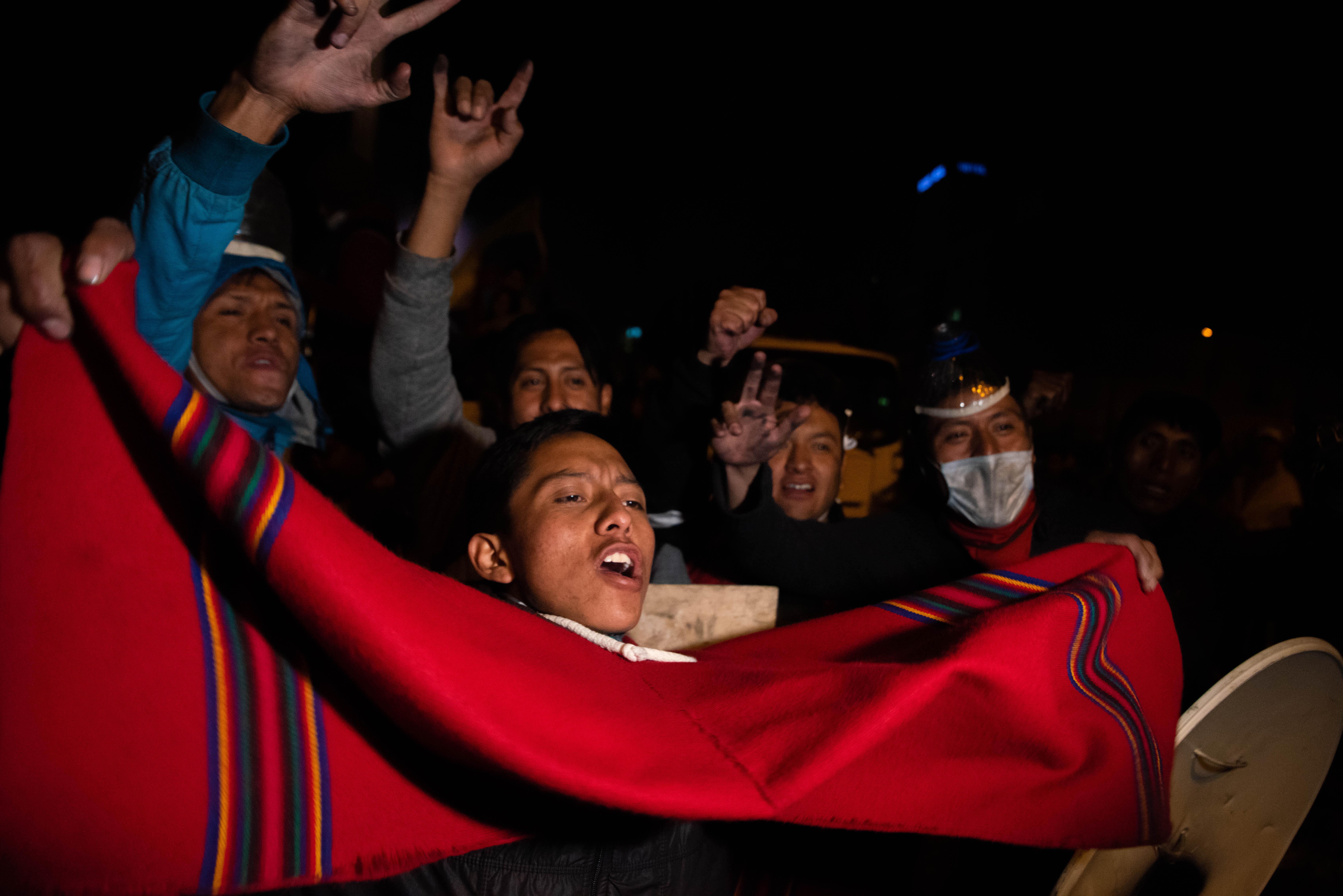 Un joven celebra en las calles de Quito con un poncho rojo.