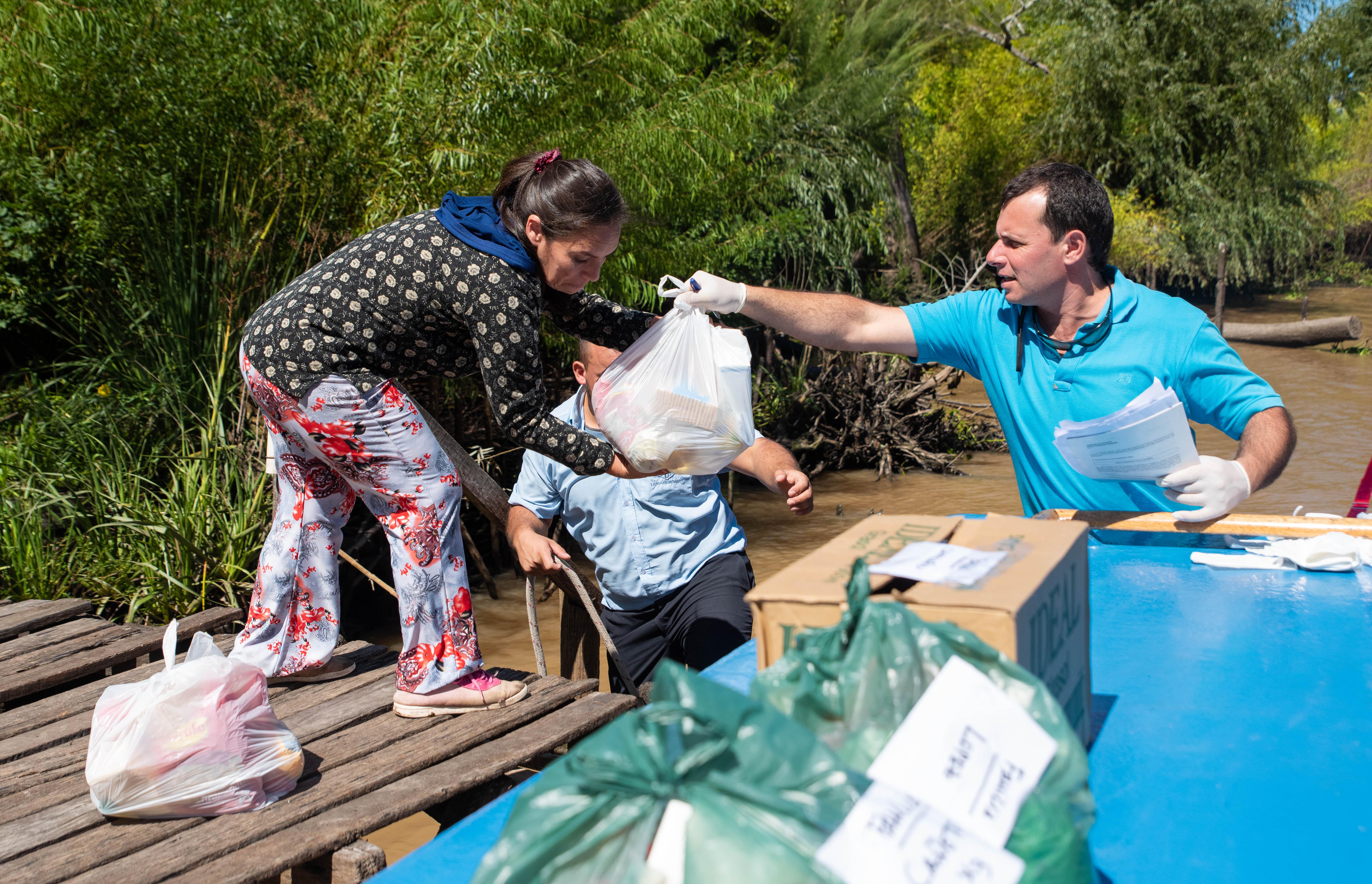 Diego le entrega una bolsa de comida a la madre de uno de sus alumnos residentes en el Delta del Tigre. (Foto: Franco Fafasuli)