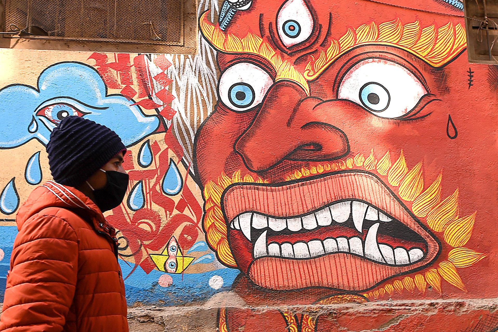 Un residente con una máscara protectora camina en el área de la Plaza Patan Durbar en Katmandú el 10 de febrero de 2020 (PRAKASH MATHEMA / AFP)