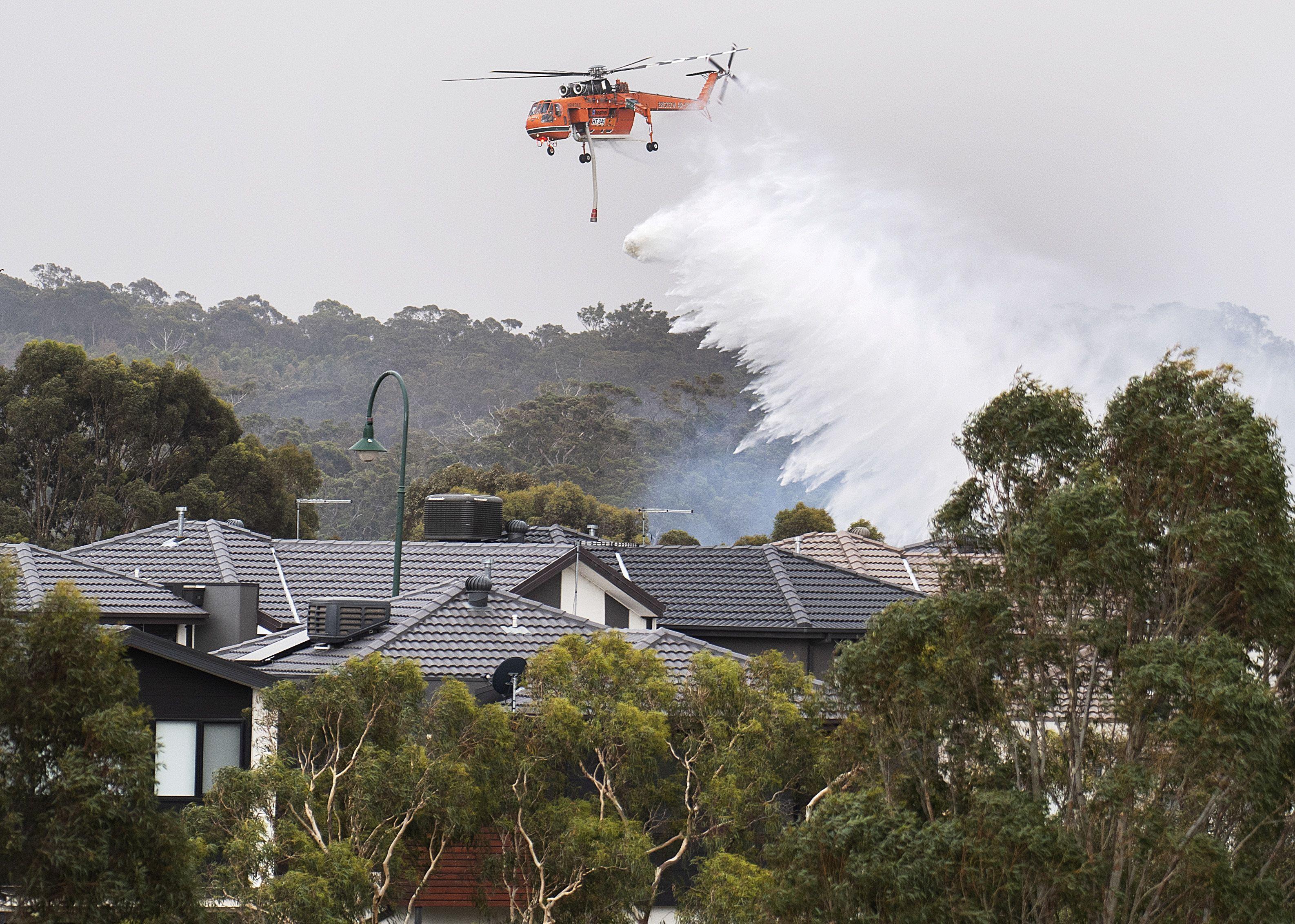 Los medios locales mostraron imágenes de bomberos sobrevolando barrios residenciales y de familias mojando sus viviendas con agua con la esperanza de poder detener el avance de las llamas