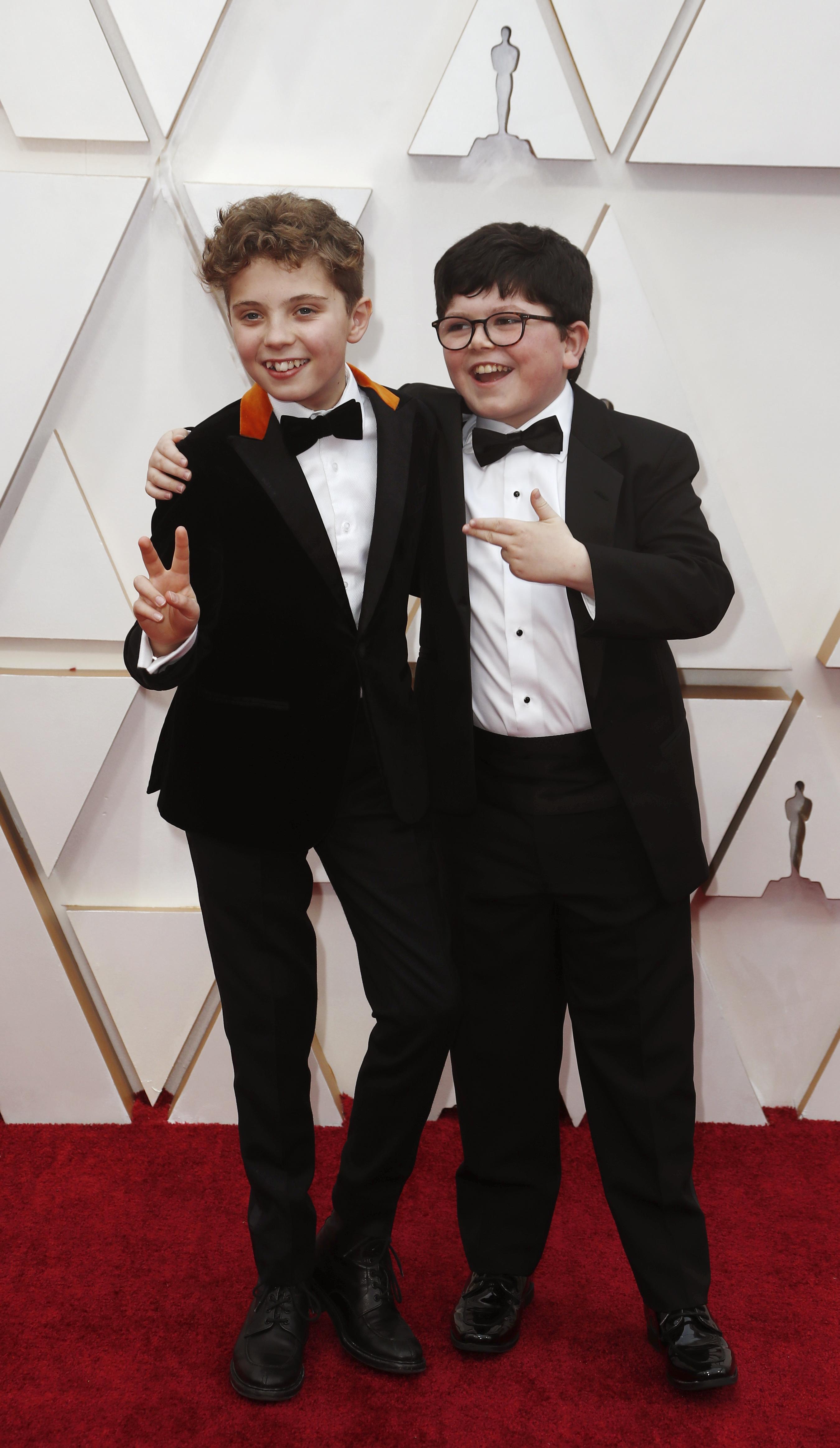 Roman Griffin Davis y Archie Yates, llegaron a la alfombra roja de los Oscar apostando al black tie con moño y camisa blanca. El distintivo fue el saco de Griffin Davis un detalle de chiffón naranja