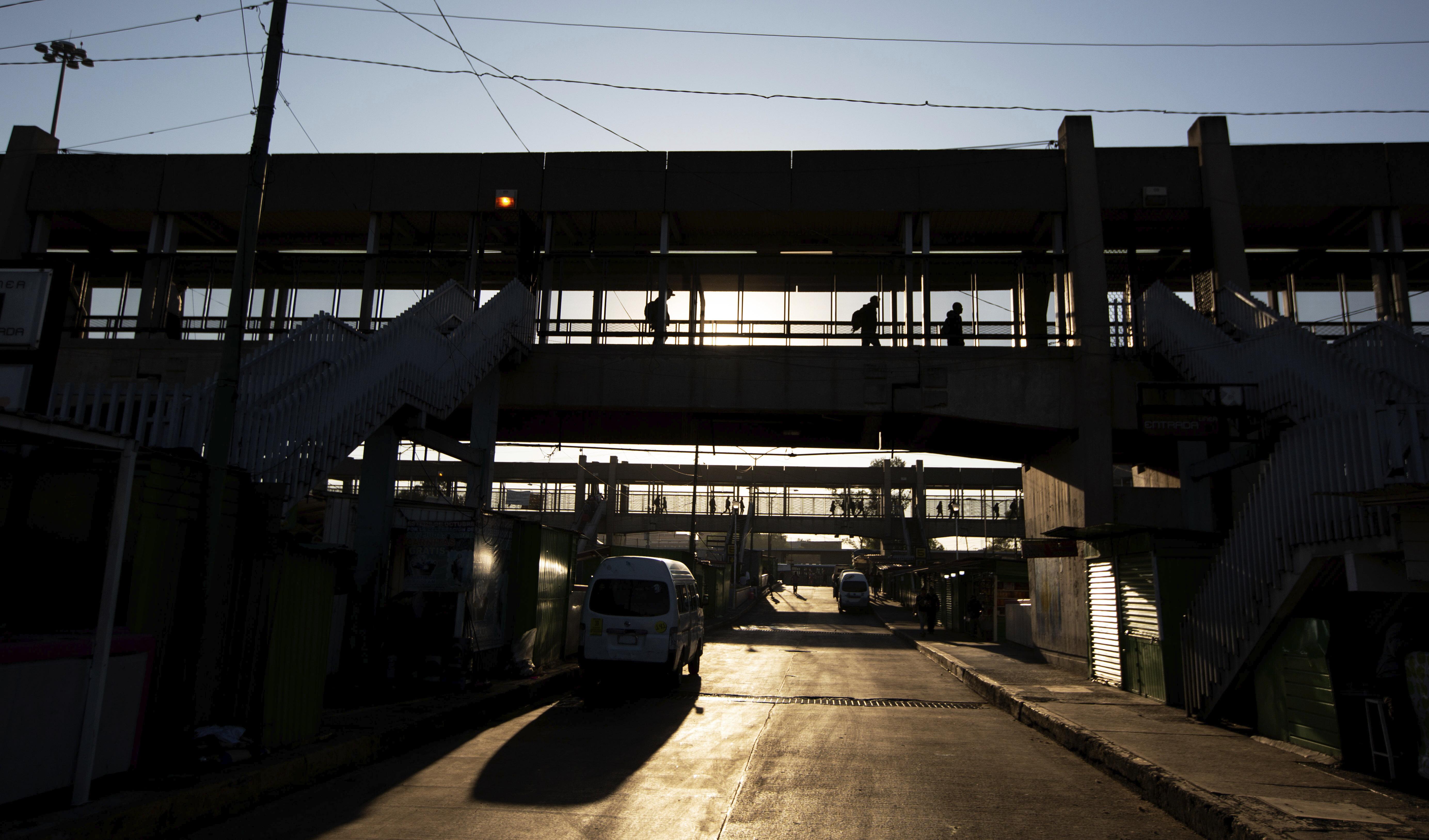 Viajeros del metro caminan por un puente peatonal con el cielo matutino en la Ciudad de México, el miércoles 25 de marzo de 2020. La capital de México ha cerrado museos, bares, gimnasios, iglesias, teatros y otros negocios no esenciales que reúnen una gran cantidad de personas, en un intento por frenar la propagación del nuevo coronavirus.