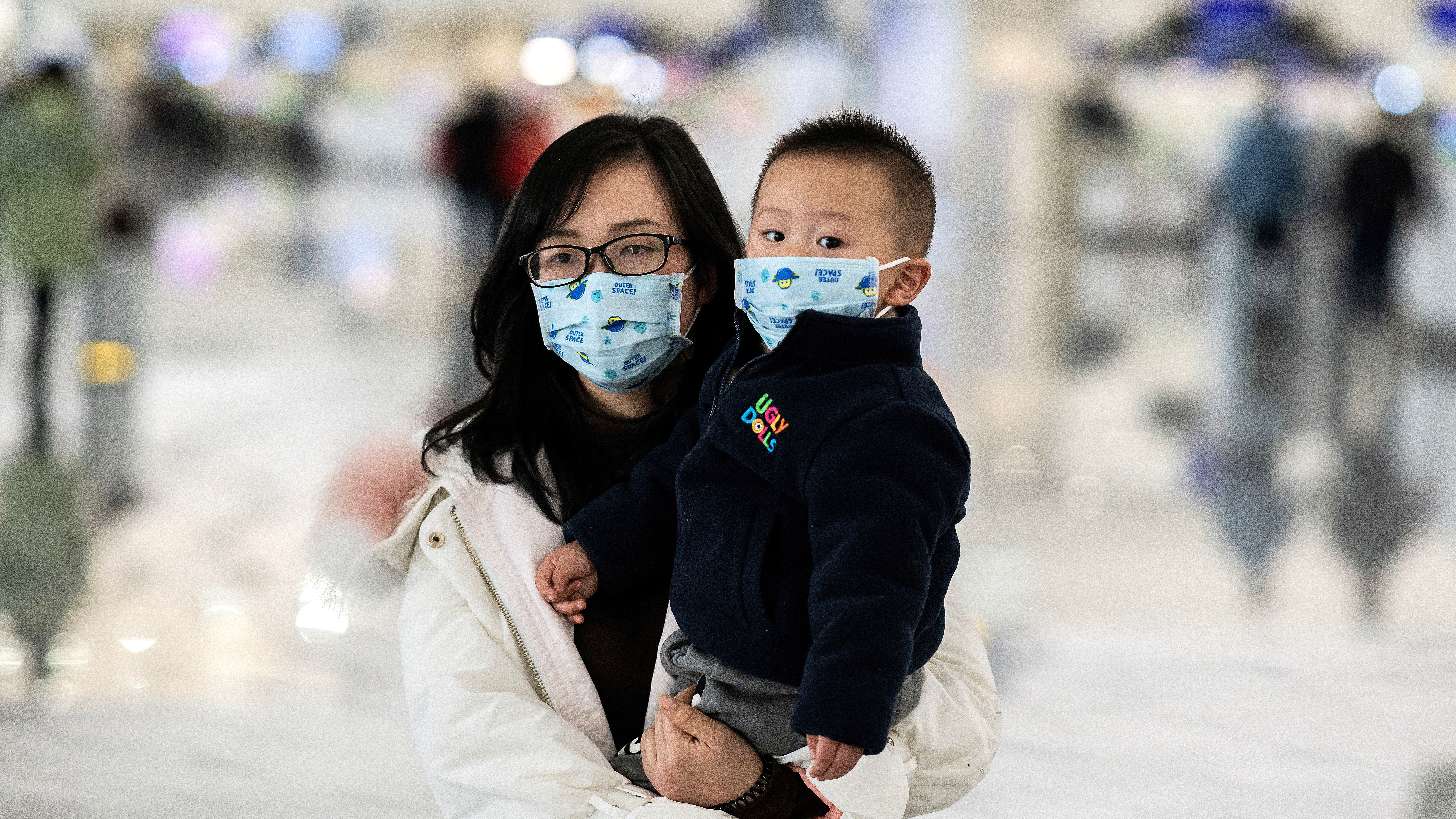 Una mujer y un niño con máscaras protectoras caminan hacia los mostradores de facturación en el aeropuerto internacional de Daxing en Beijing el 21 de enero de 2020. (Foto por NICOLAS ASFOURI / AFP)