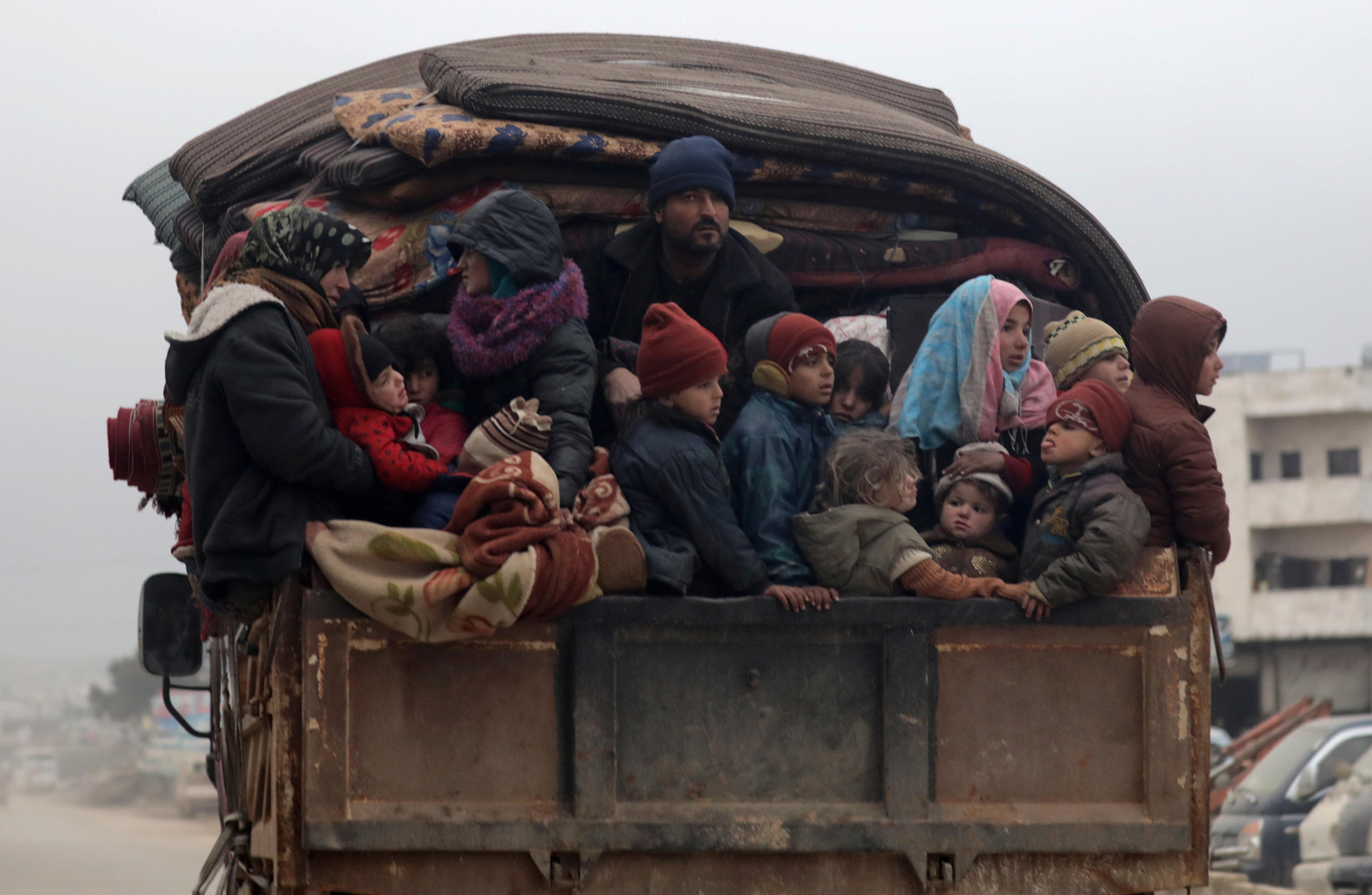 Los miembros de una familia observan desde la parte trasera del camión que los aleja del frente