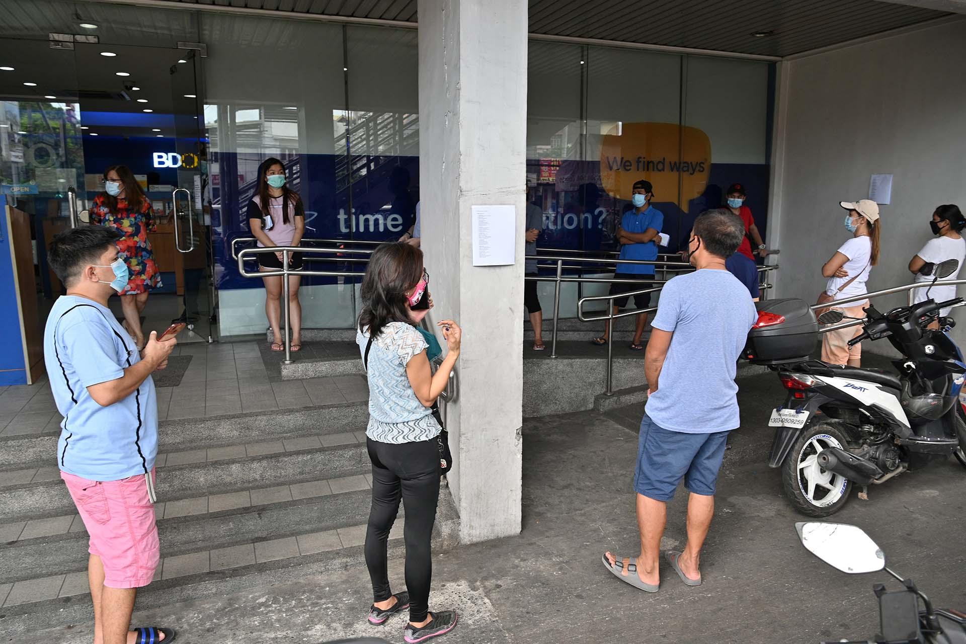 Clientes hacen fila para ingresar en una sucursal bancaria en Manila, Filipinas.